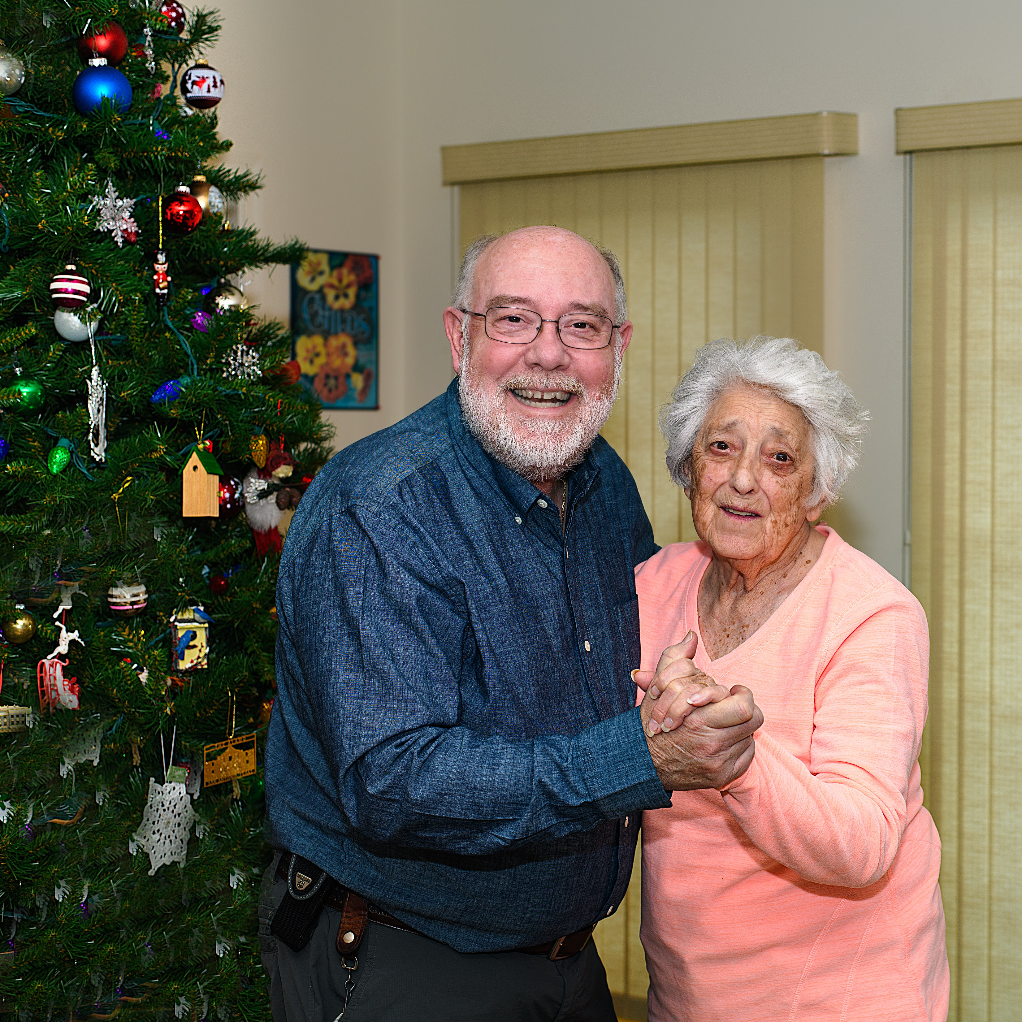 man and woman holding each other's hands beside Christmas tree