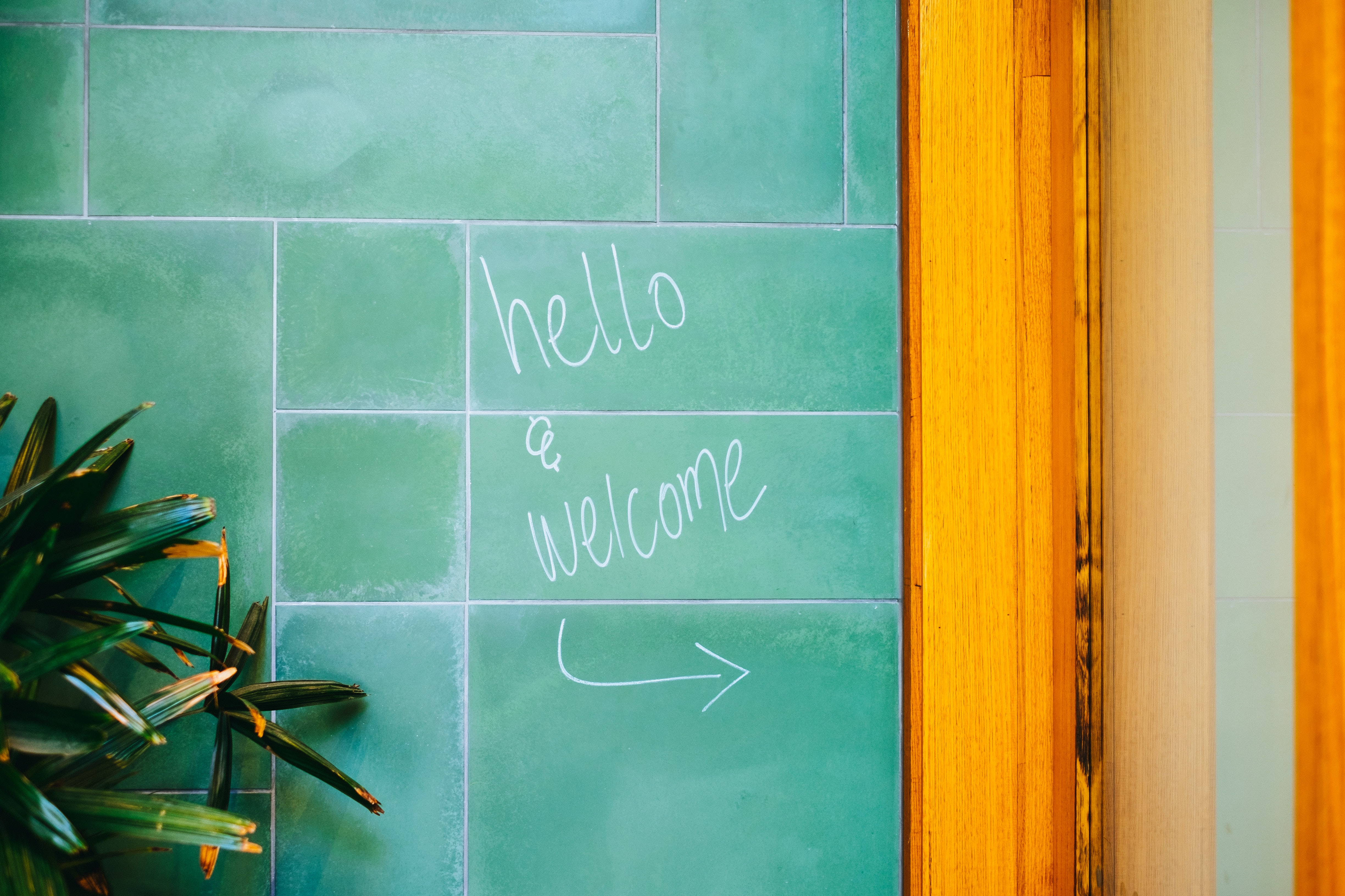 green tile wall with hello & welcome text