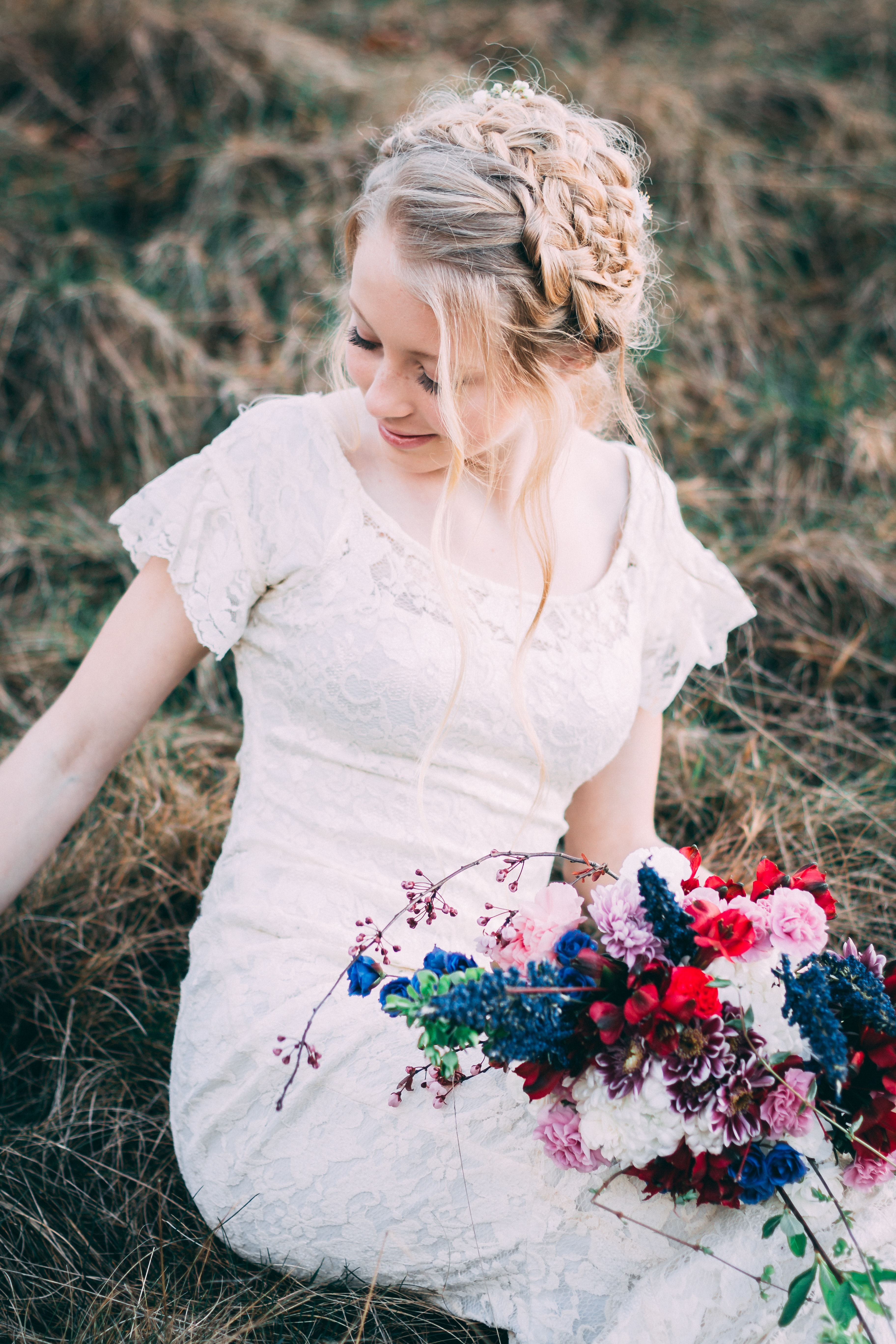 woman holding bouquet of flowers siting on hay