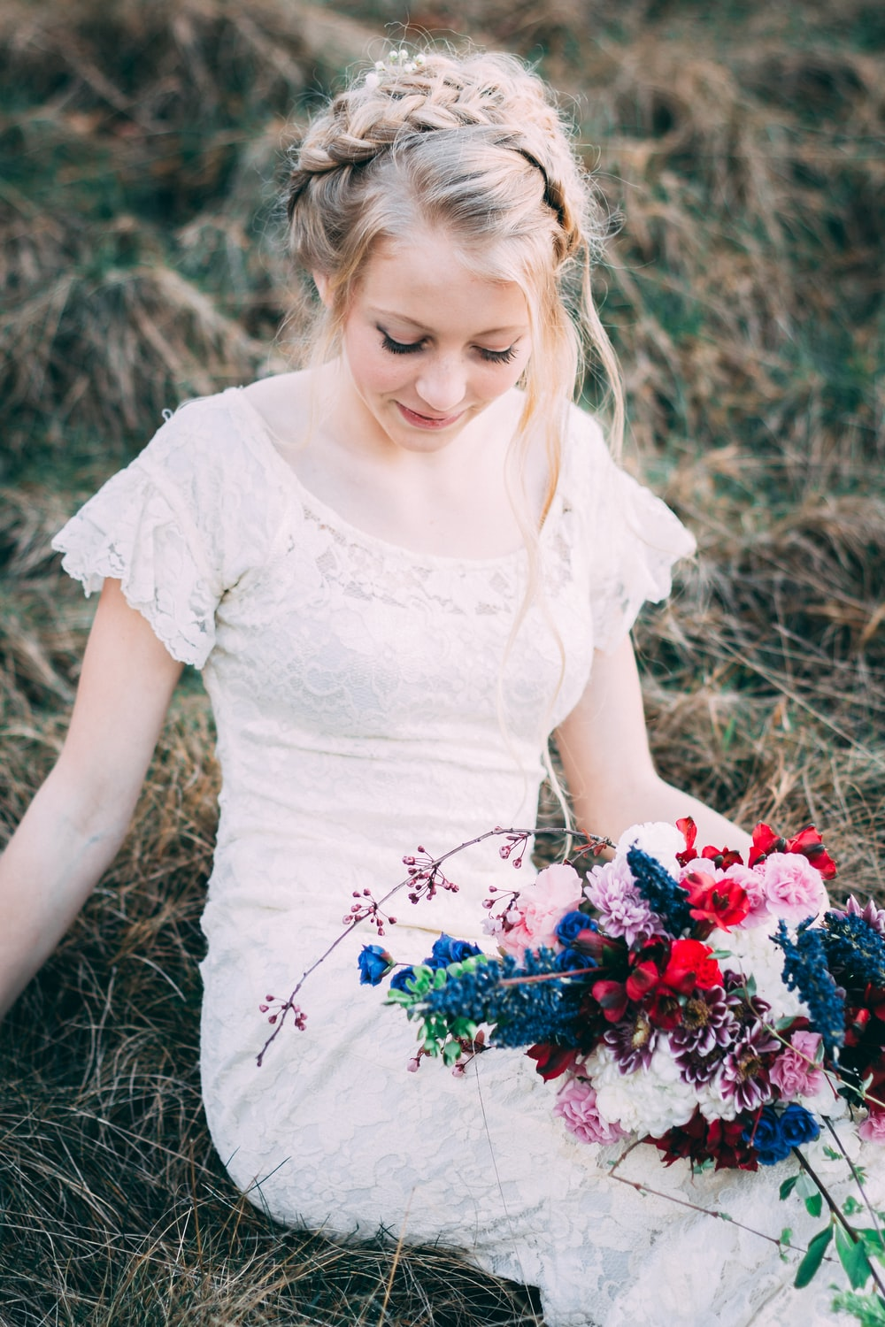 woman wearing white lace dress with flower bouquet sitting on grass at daytime