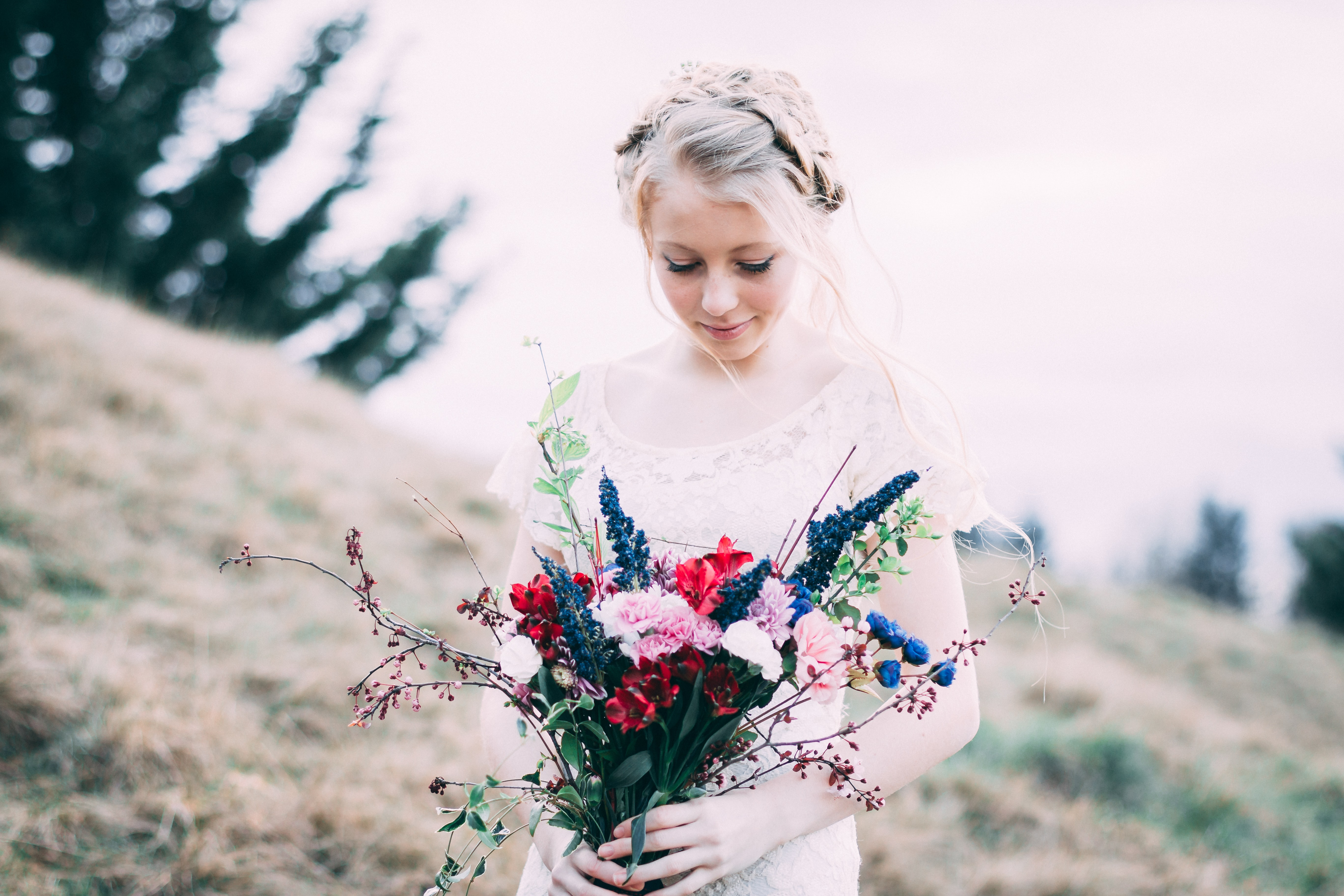 girl holding assorted bouquet flowers while looking down