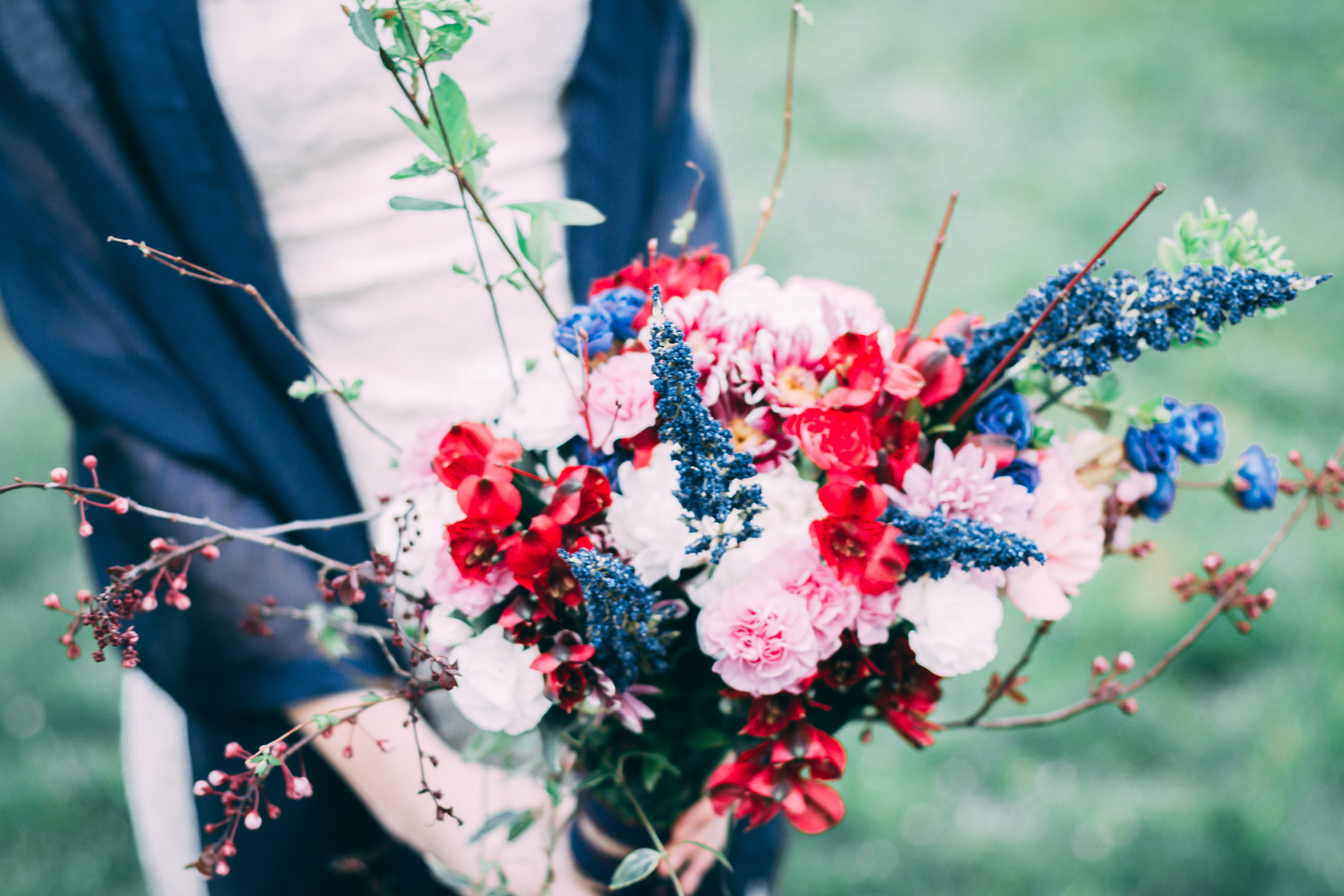 person holding bouquet of pink, red, and blue petaled flowers