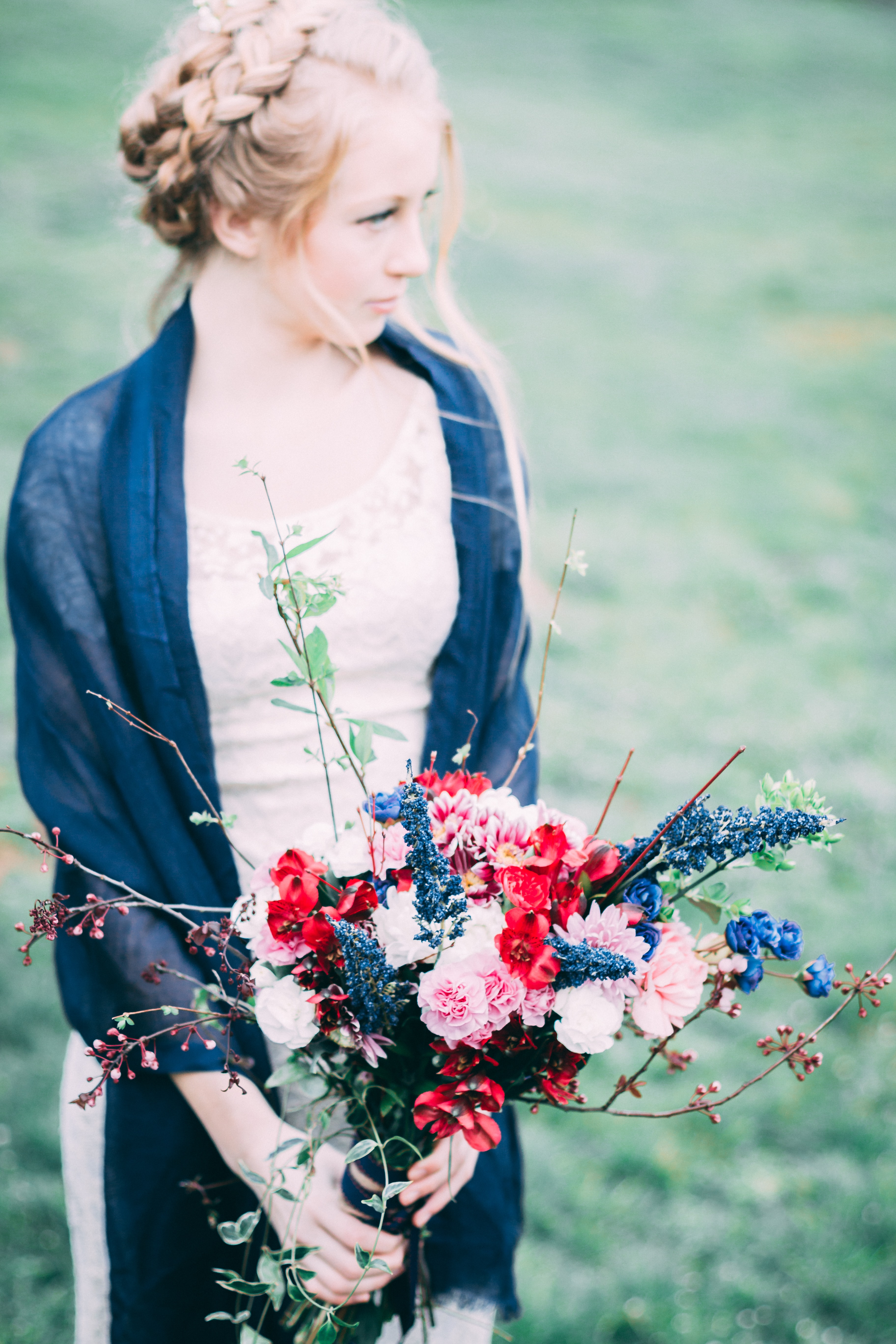 women wearing blue cardigan holding flowers