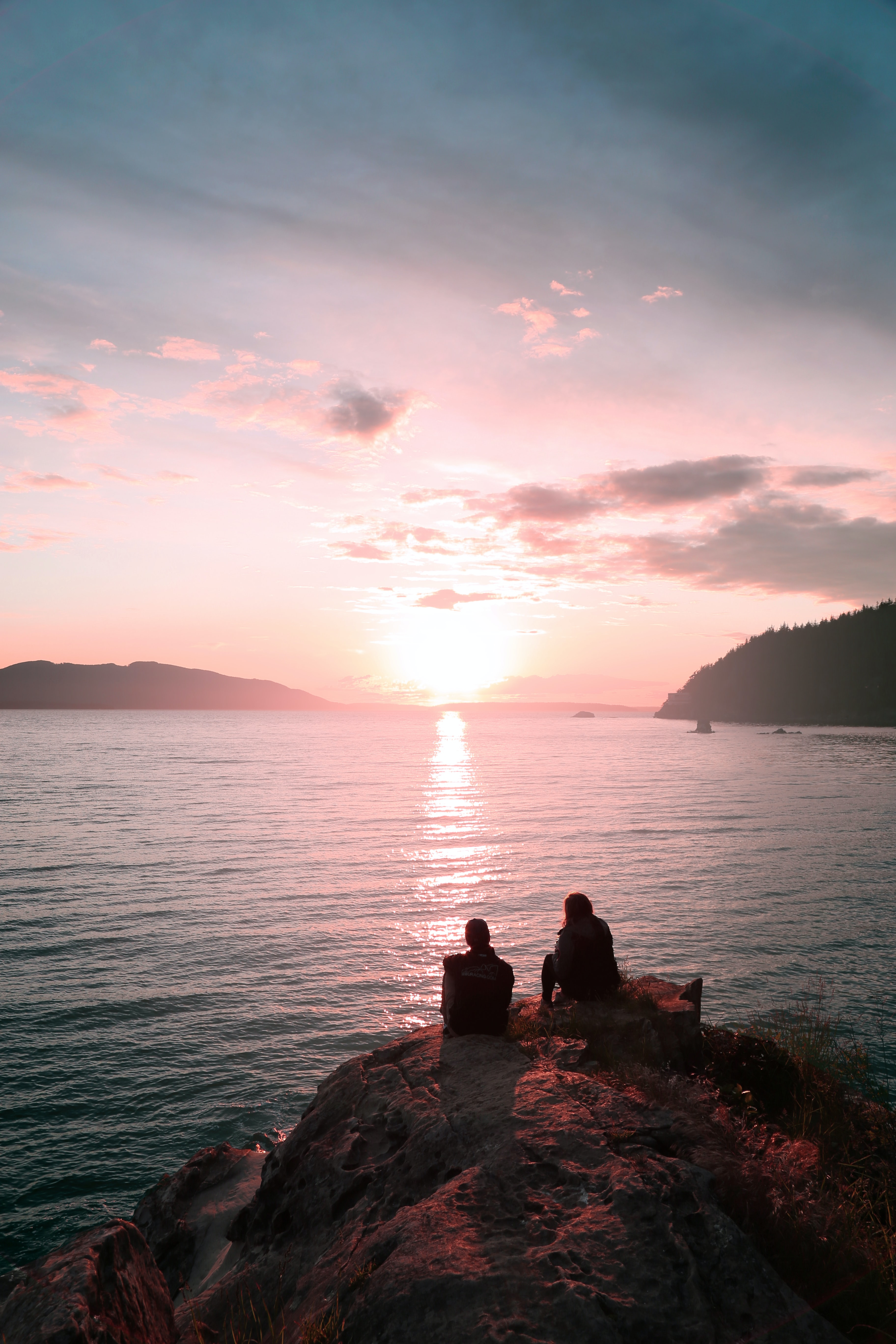 two persons sitting on rock during dawn