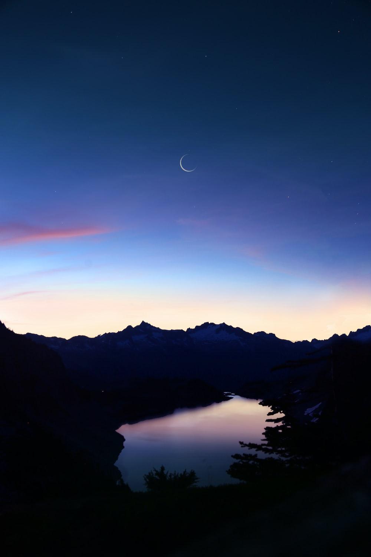 birds eye-view of lake under crescent moon
