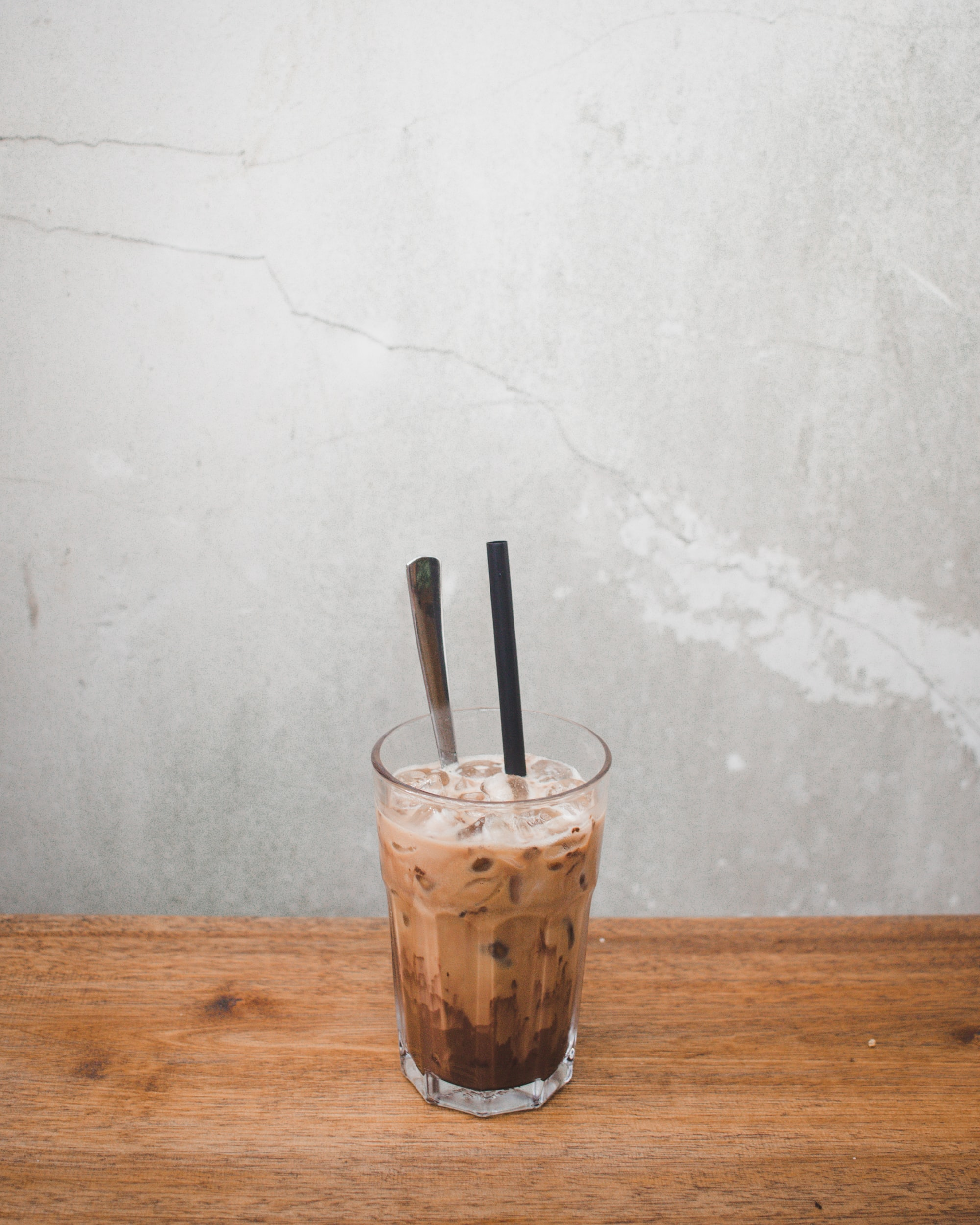 clear crystal glass with beverage and plastic sipping straw