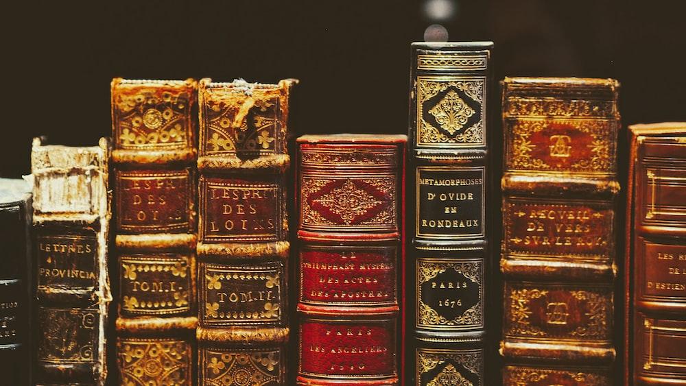 seven hardbound books on black surface