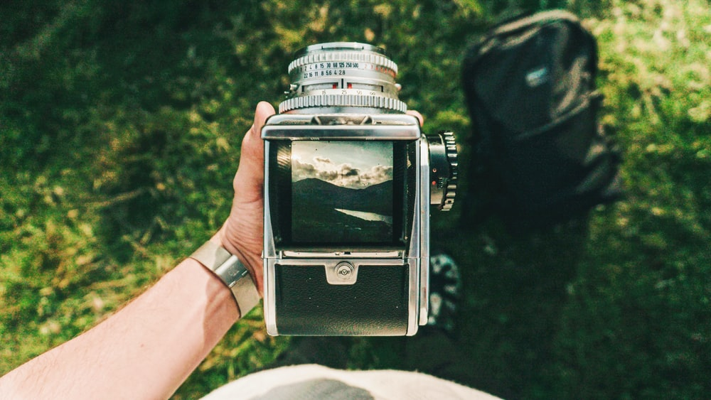 person holding black and gray folding camera