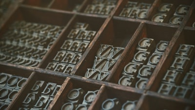 gray assorted-letter jewelries in brown wooden organizer boxes