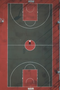 person lying in the middle of basketball court