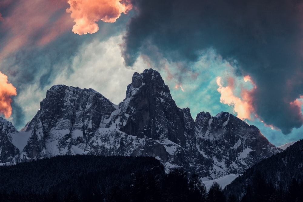 closeup photo of grey mountains covered by snow during golden hour