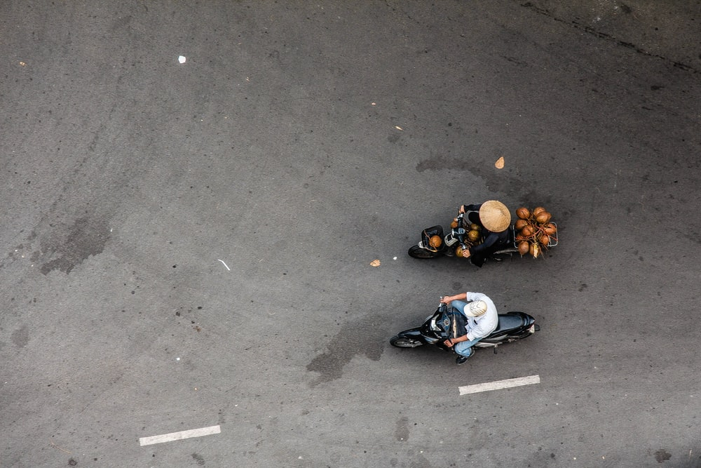 two people riding motorcycle on concrete road