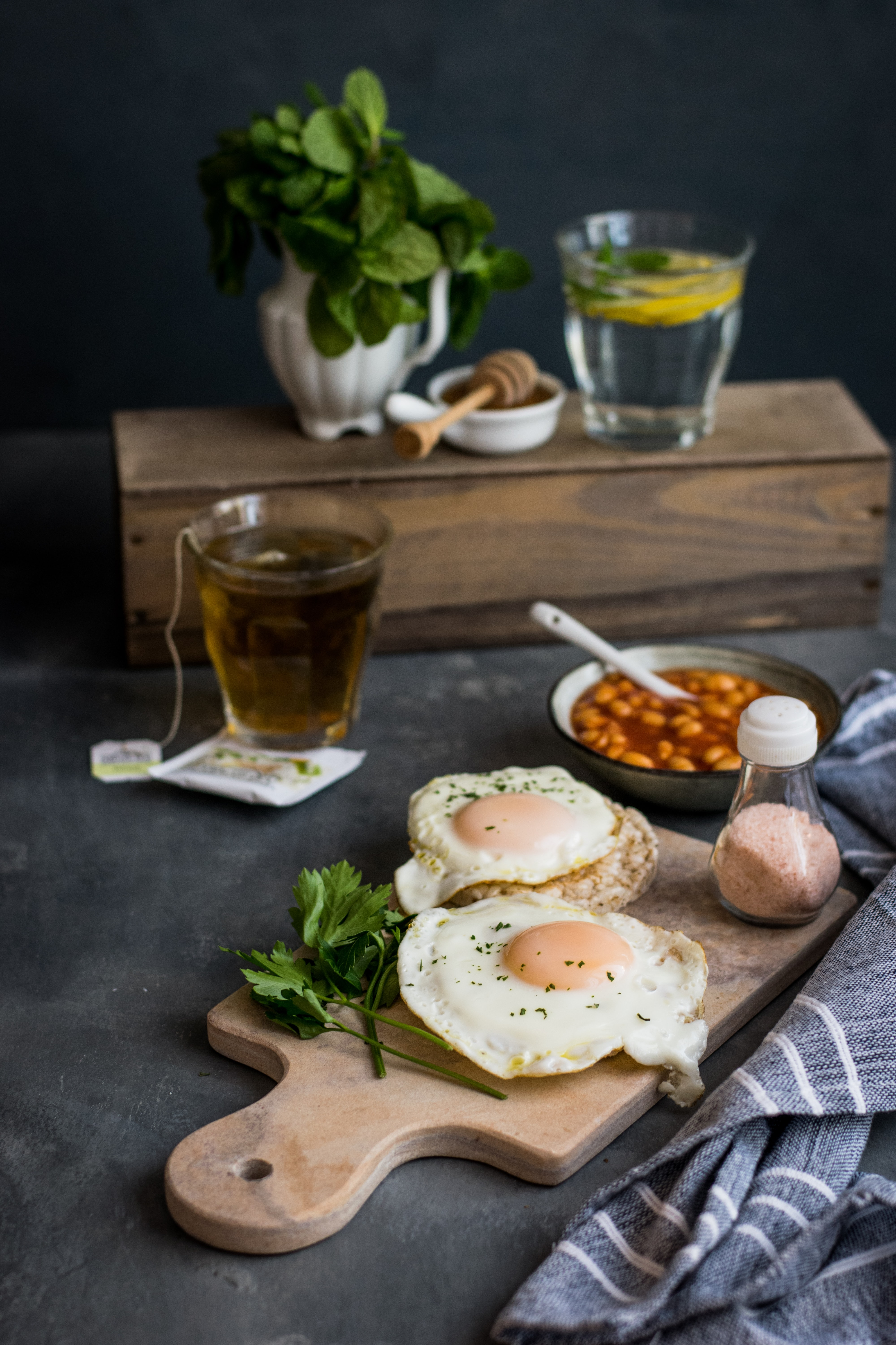 two fried eggs on brown chopping board near spices