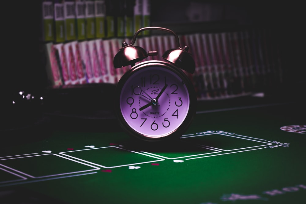 silver twin bell alarm clock on green table