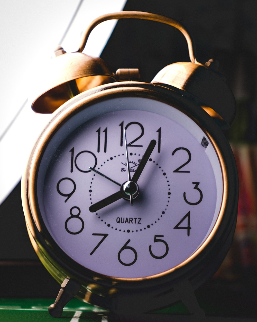 silver twin-bell alarm clock at 8:05