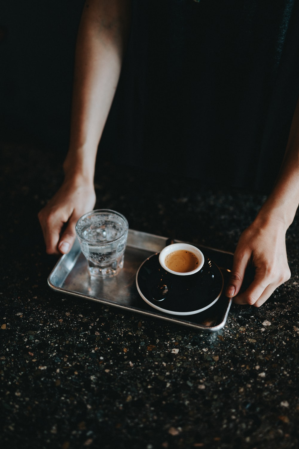 person holding tray with drinking glass and coffee cup