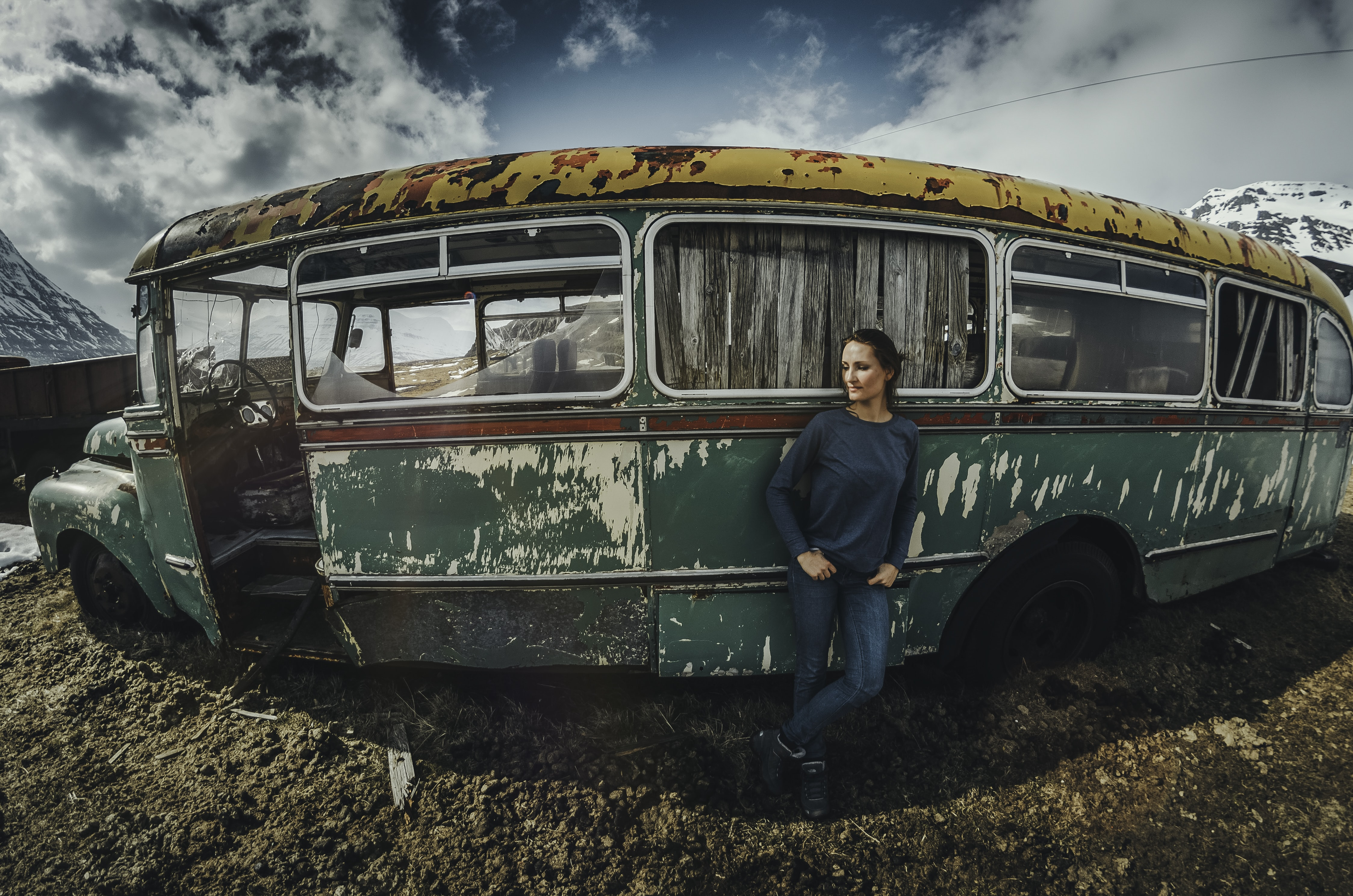 woman leaning on green bus under blue sky