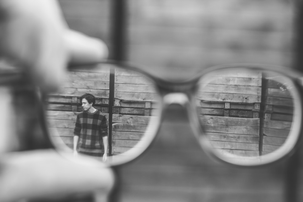 grayscale photo of man using by glasses