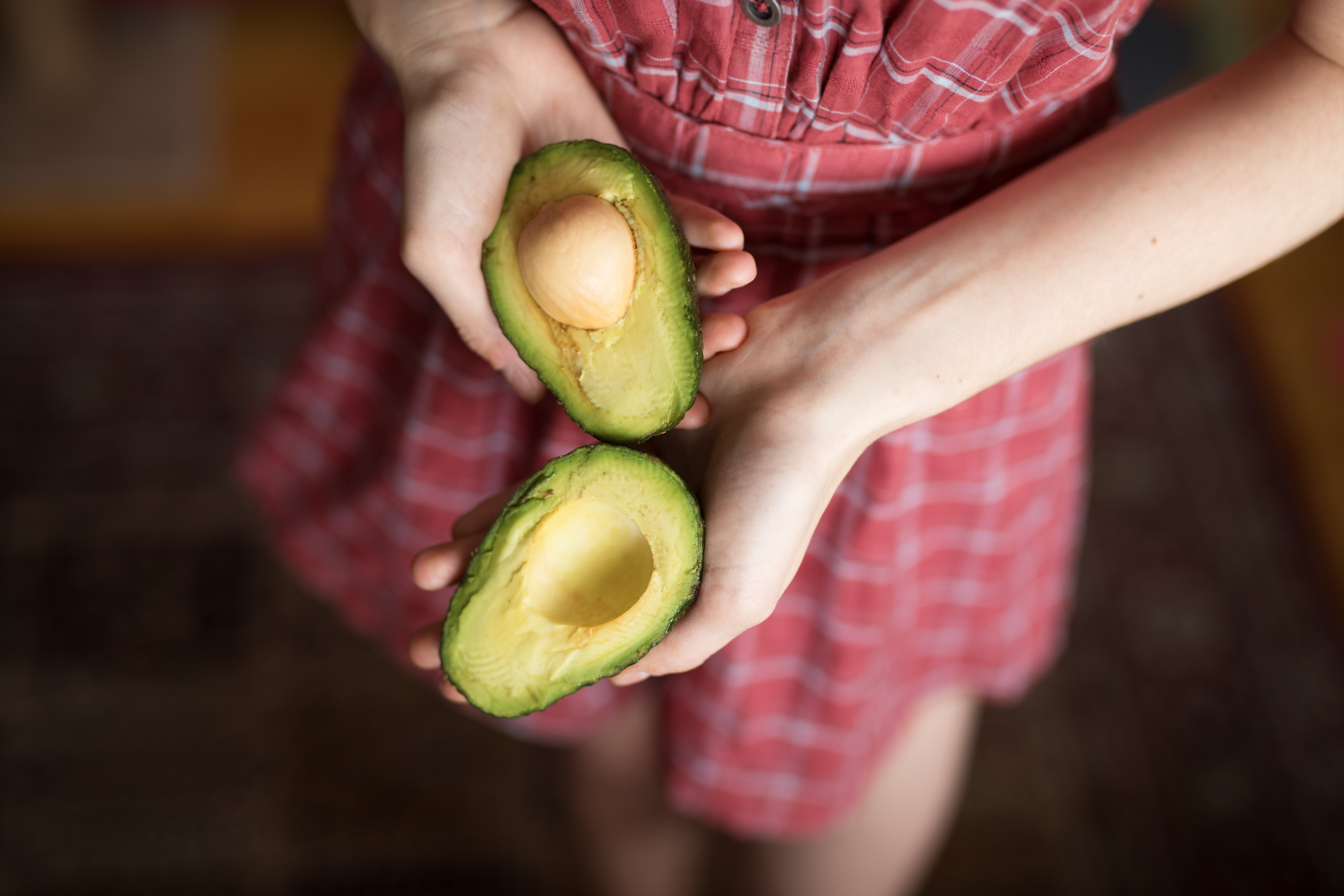 person holding two sliced avocados