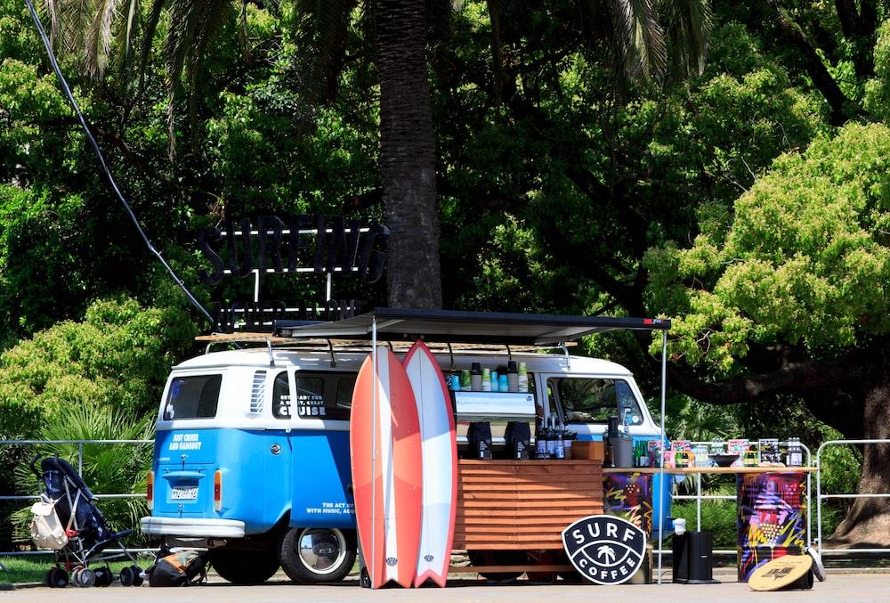 blue Volkswagen Samba beside two surfboards