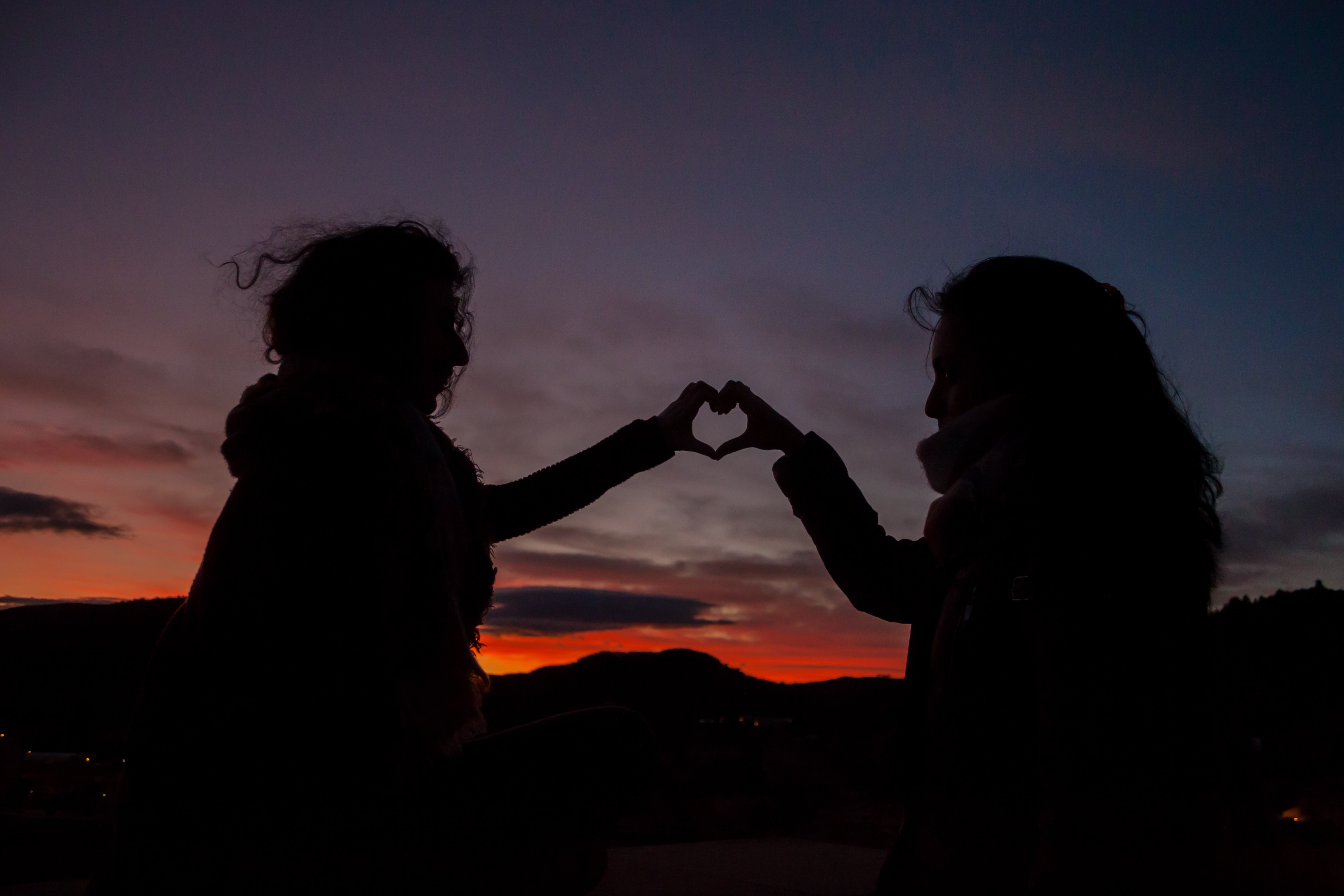 silhouette of persons doing heart hand