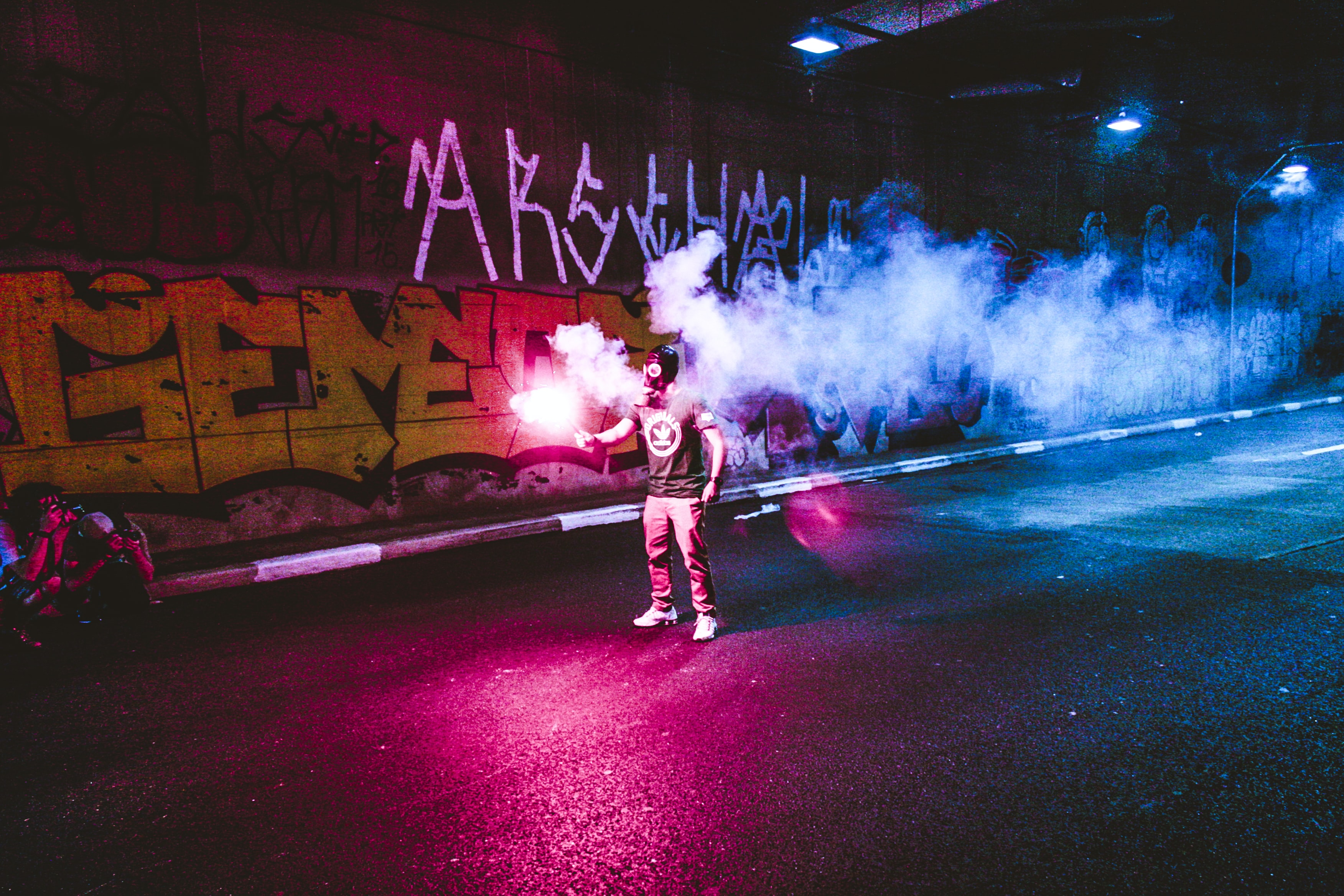 person standing holding flare in road