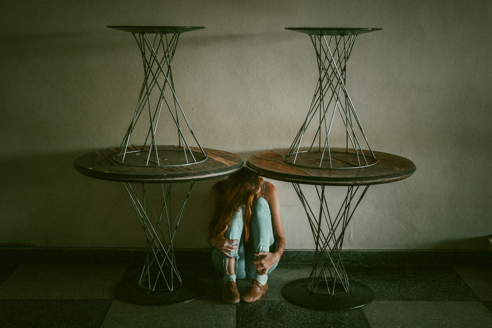 woman between and under round brown wooden pedestal dining tables