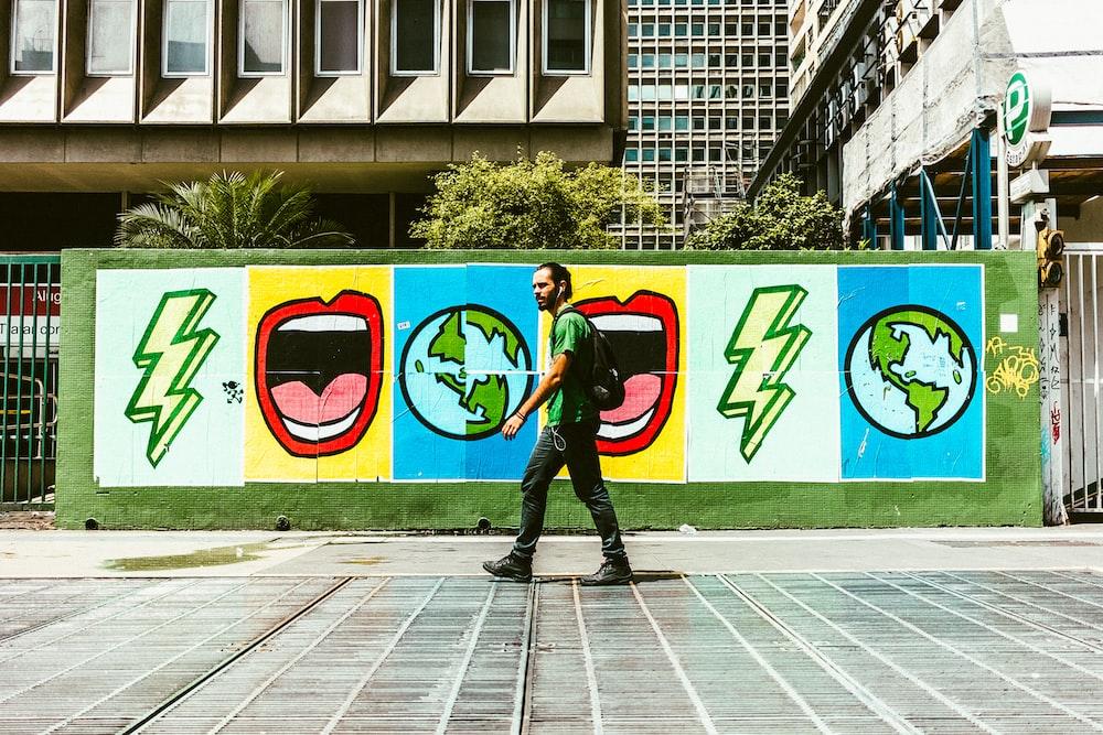man walking on street near graffiti wall during daytime