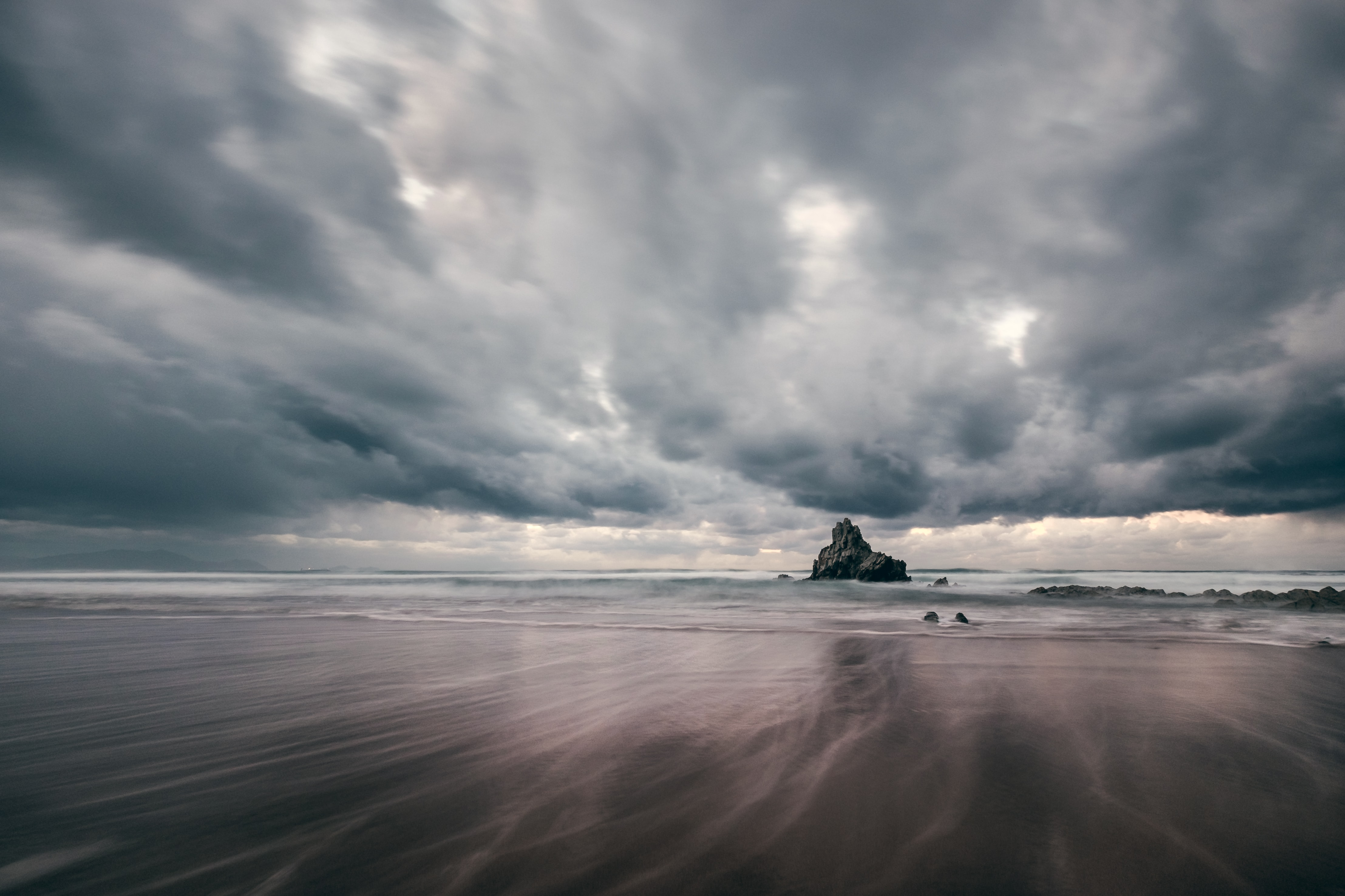 black rock formation on sea under gray clouds