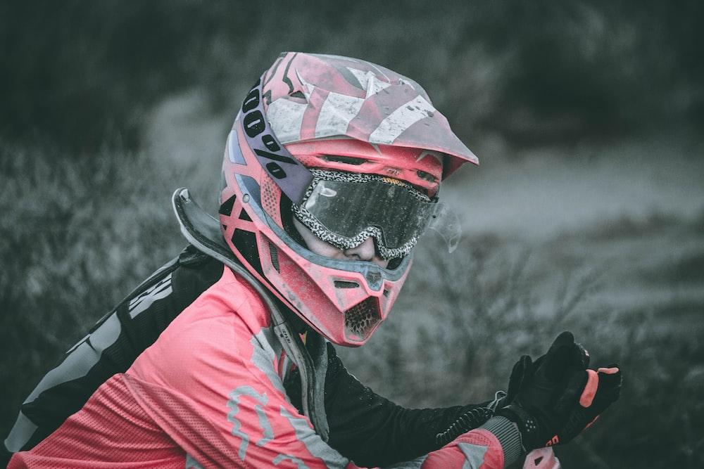 closeup photo of man wearing red motocross helmet