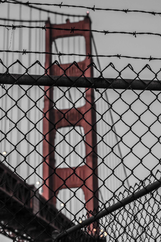 photo of diamond link fence near red bridge at daytime