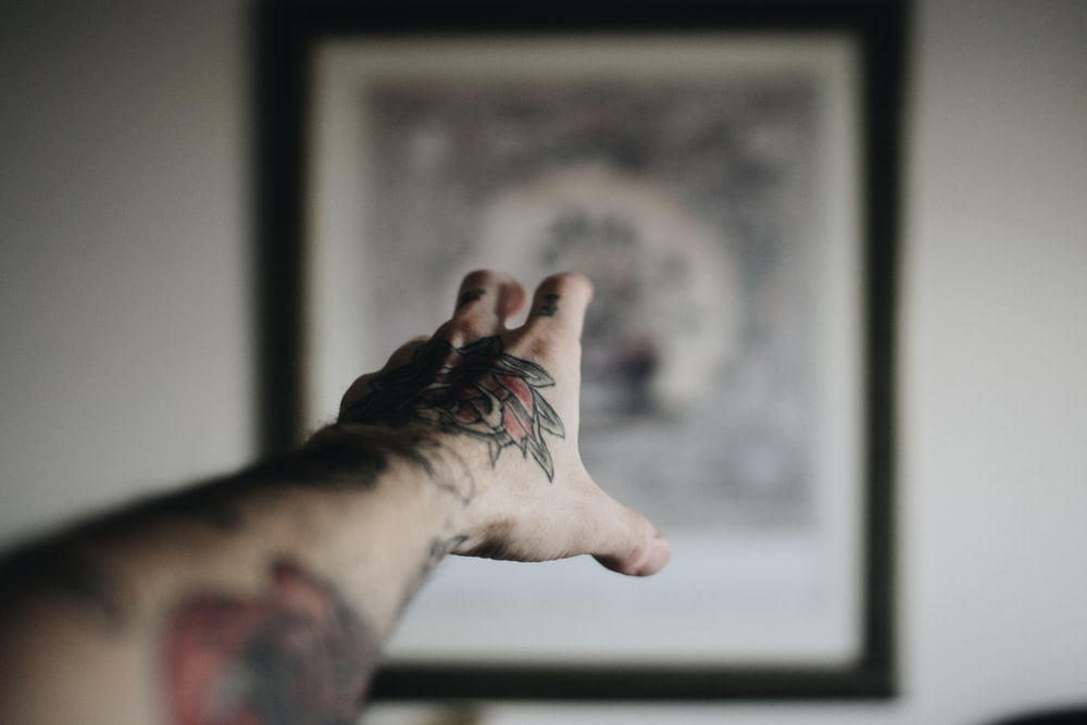 person reaching out on painting