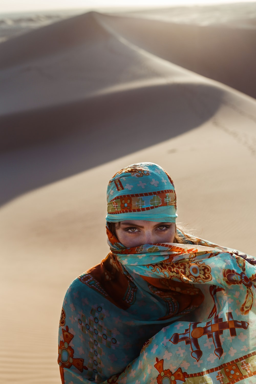 high-angle of woman walking on desert