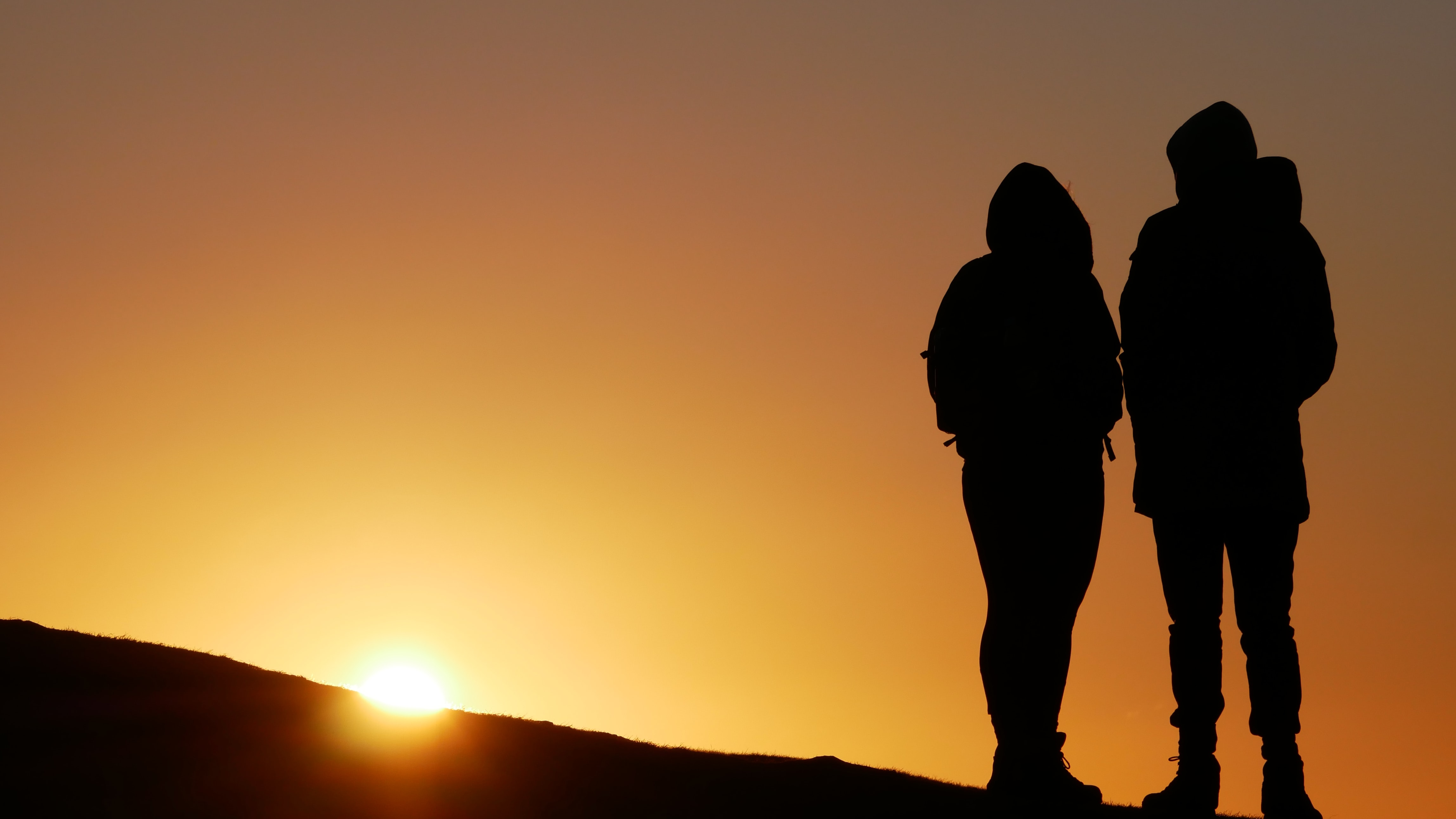 silhouette of people on top of hill during sunset