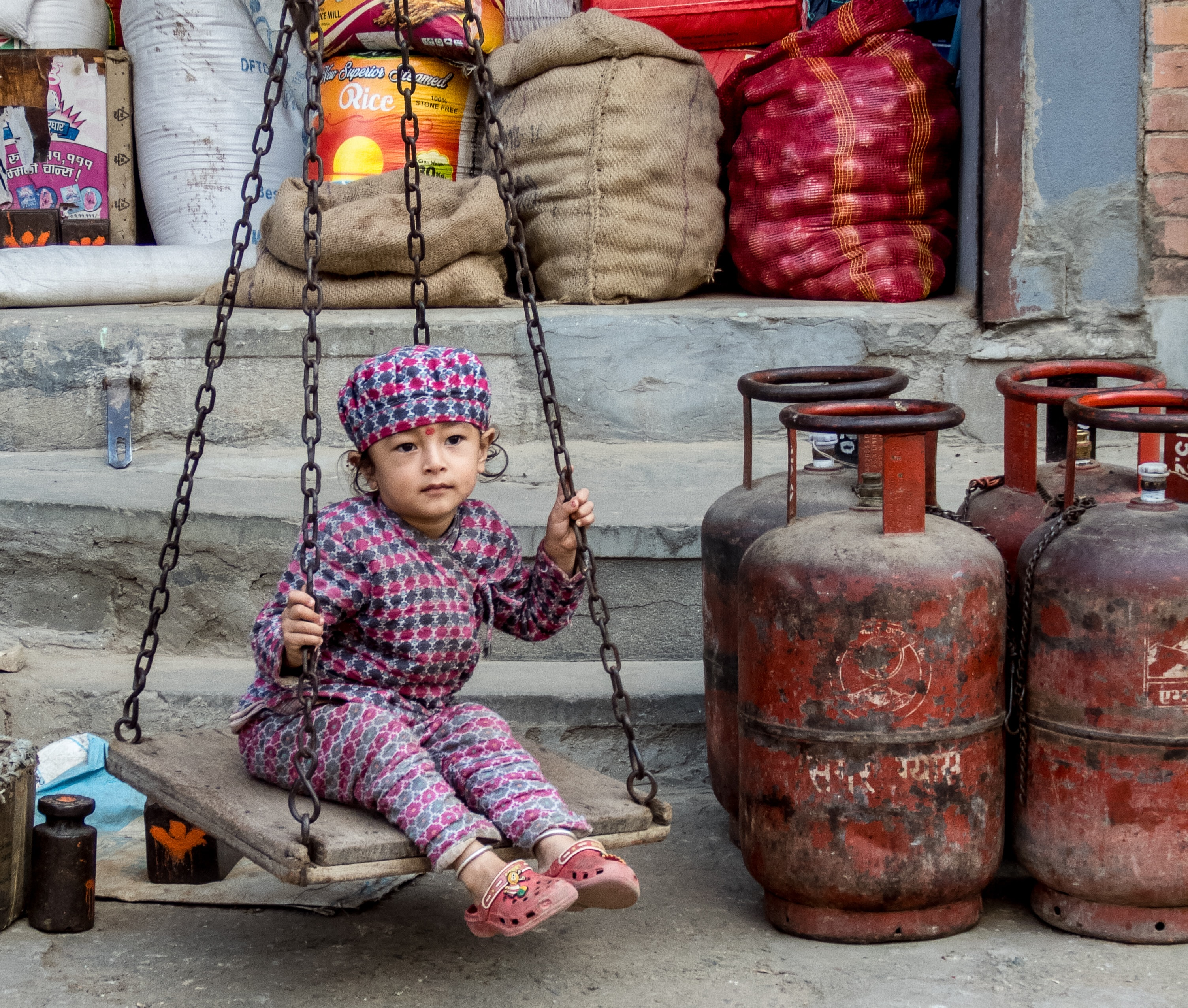girl sitting on swing near cylinder tanks