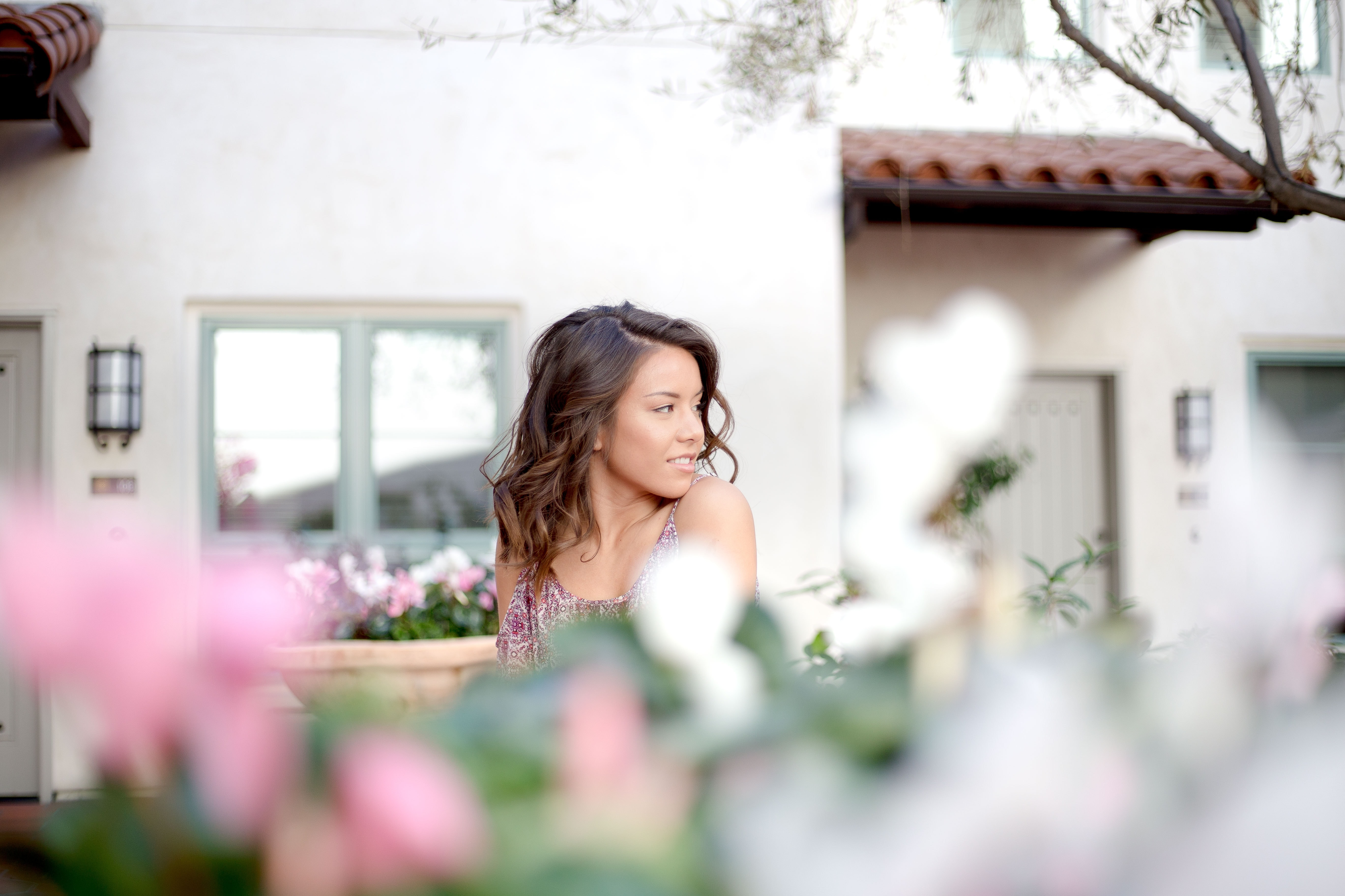 shallow focus photography of girl sitting near flowers