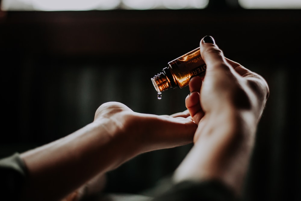 person holding amber glass bottle