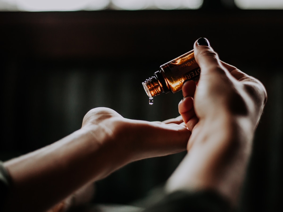 aceites esenciales, person holding amber glass bottle