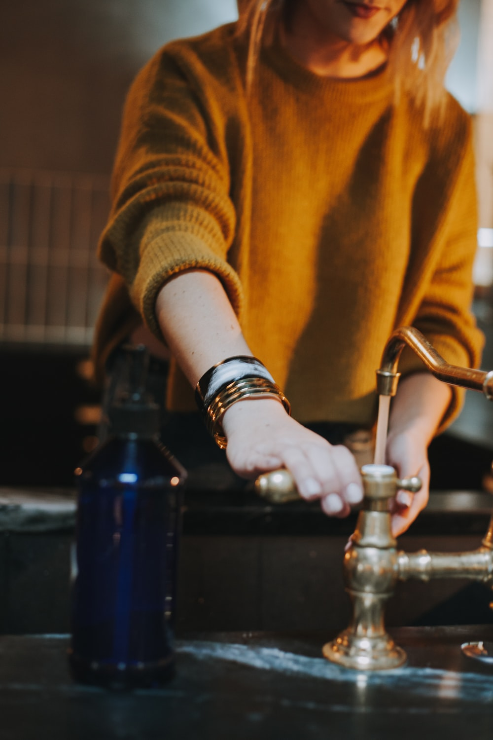 photo of woman holding brass-colored faucet