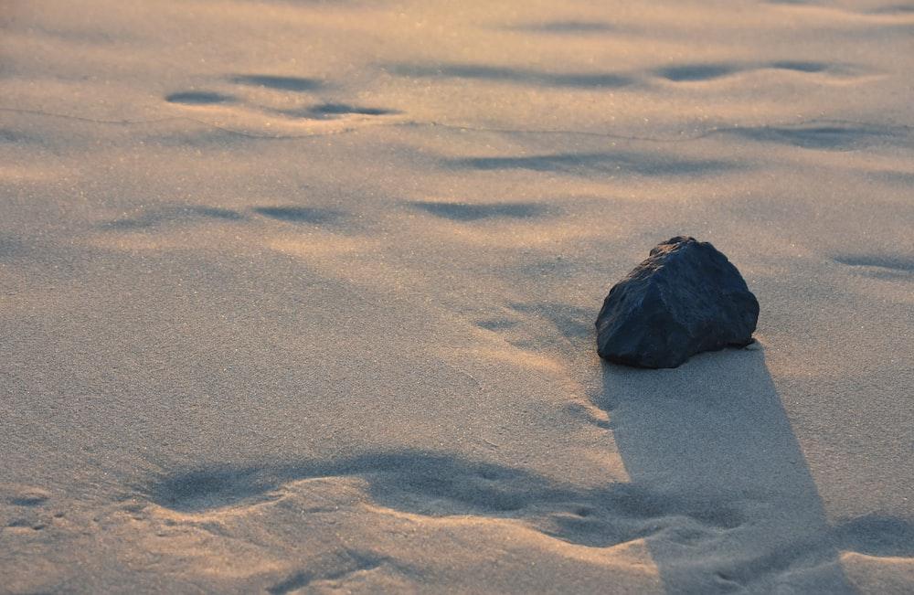 black stone fragment on white sand