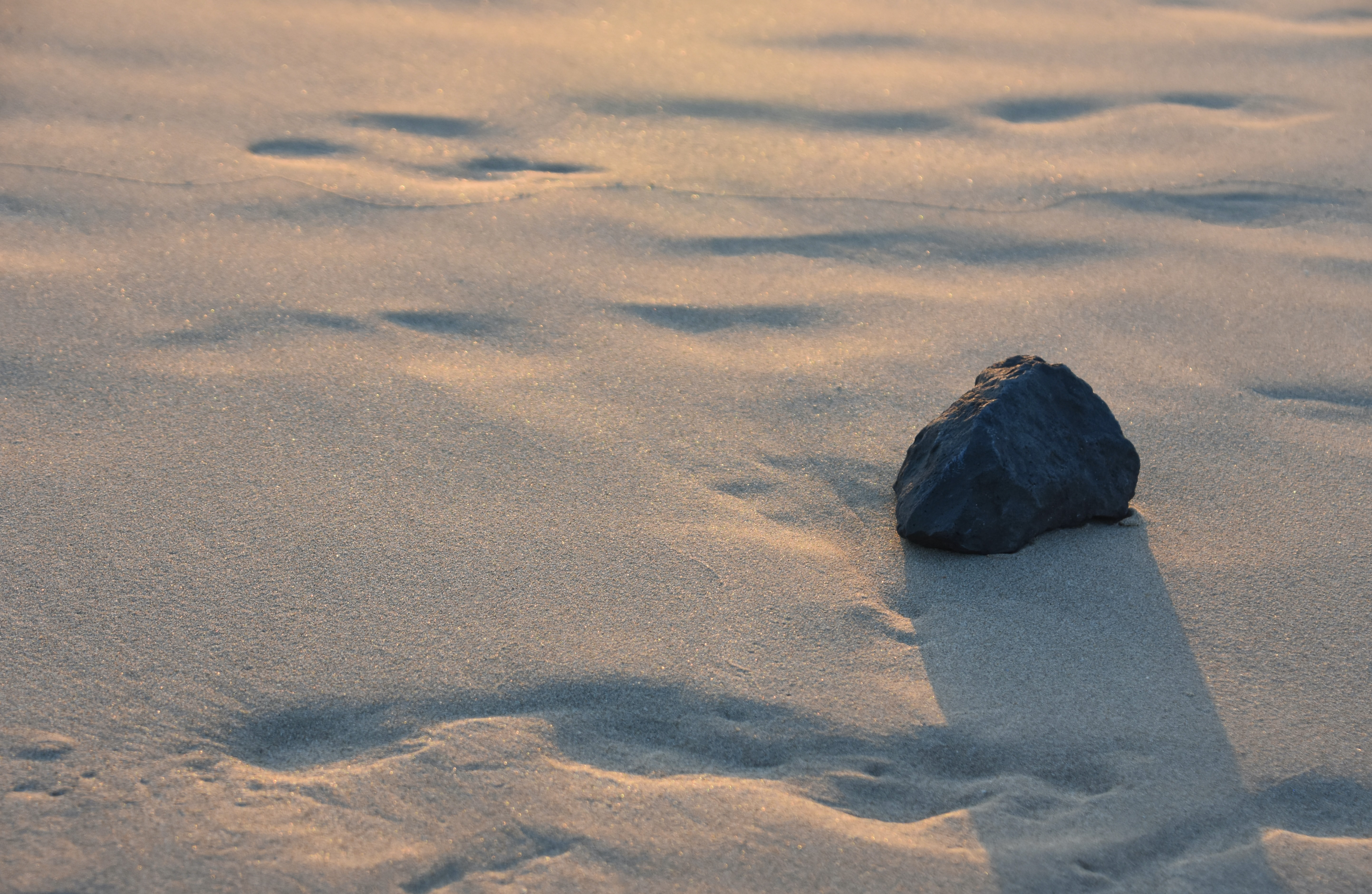 black stone fragment on white sand