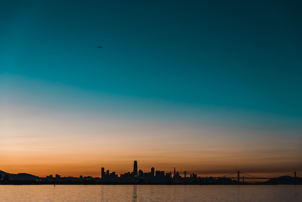 silhouette photography of buildings and body of water