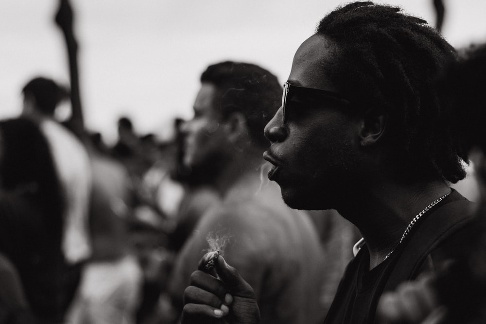 grayscale photography of man holding cigarette