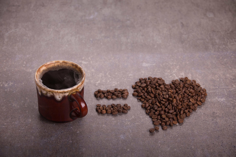 coffee bean beside brown ceramic mug