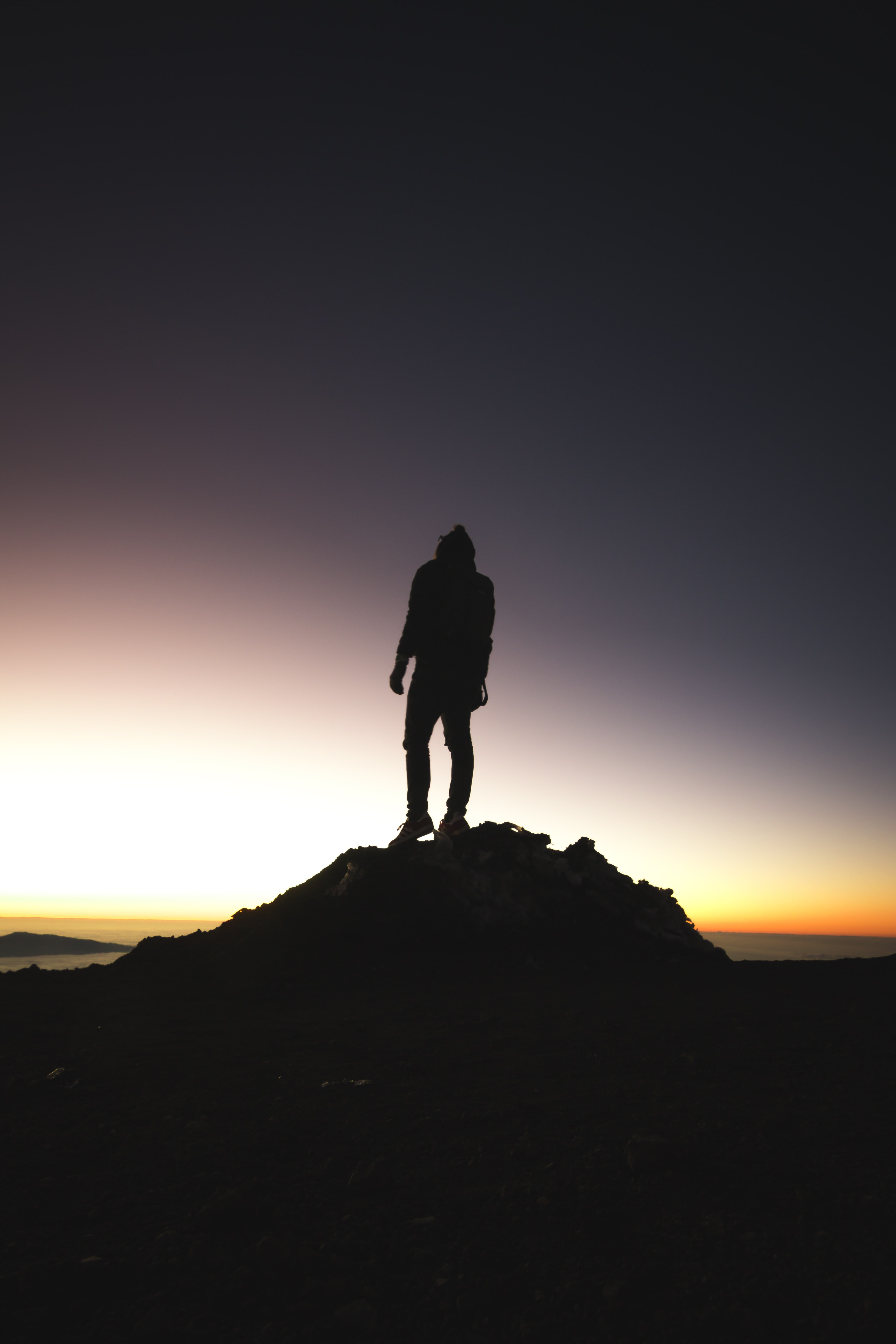 silhouette of person standing near ocean