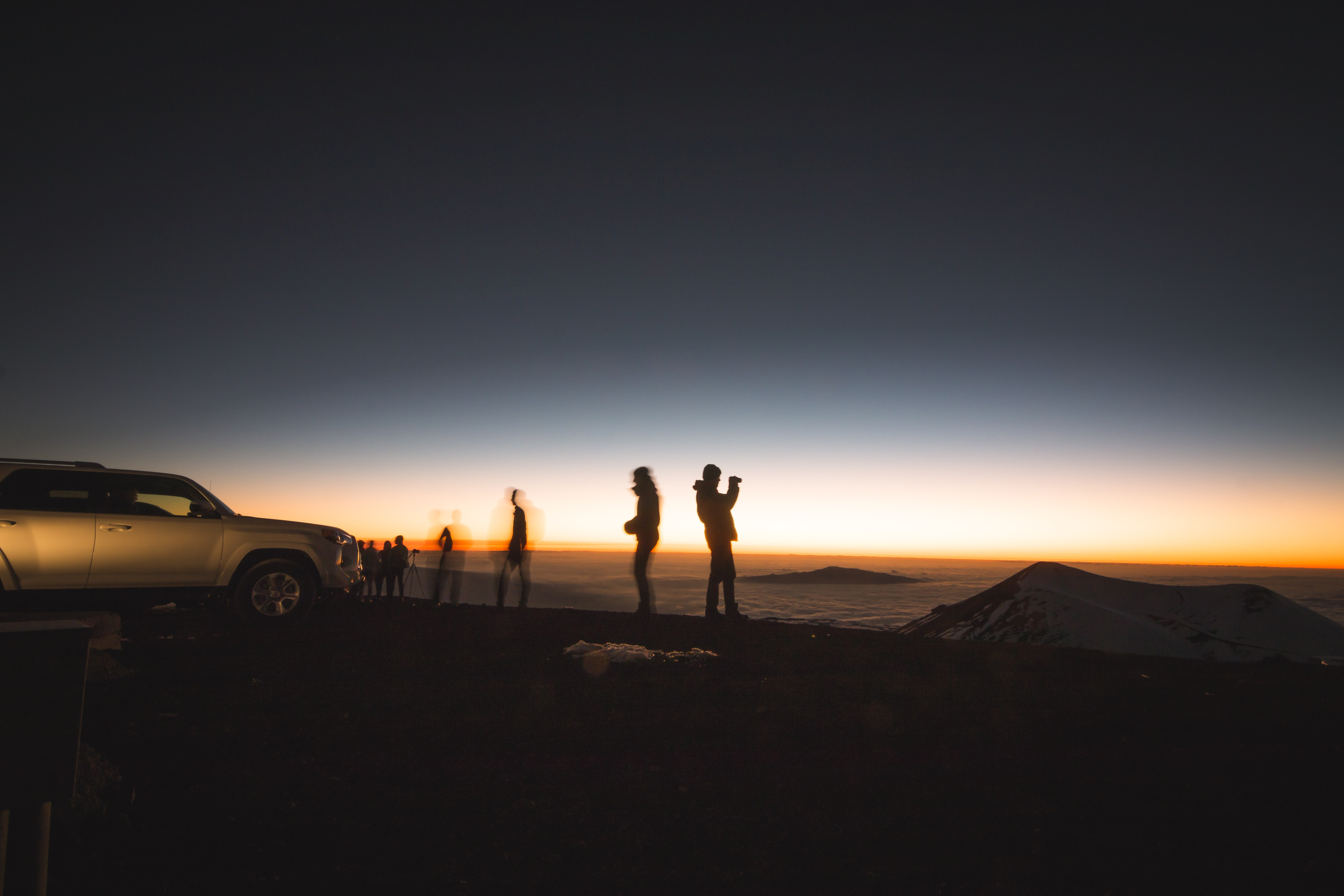 silhouette of group of people beside SUV