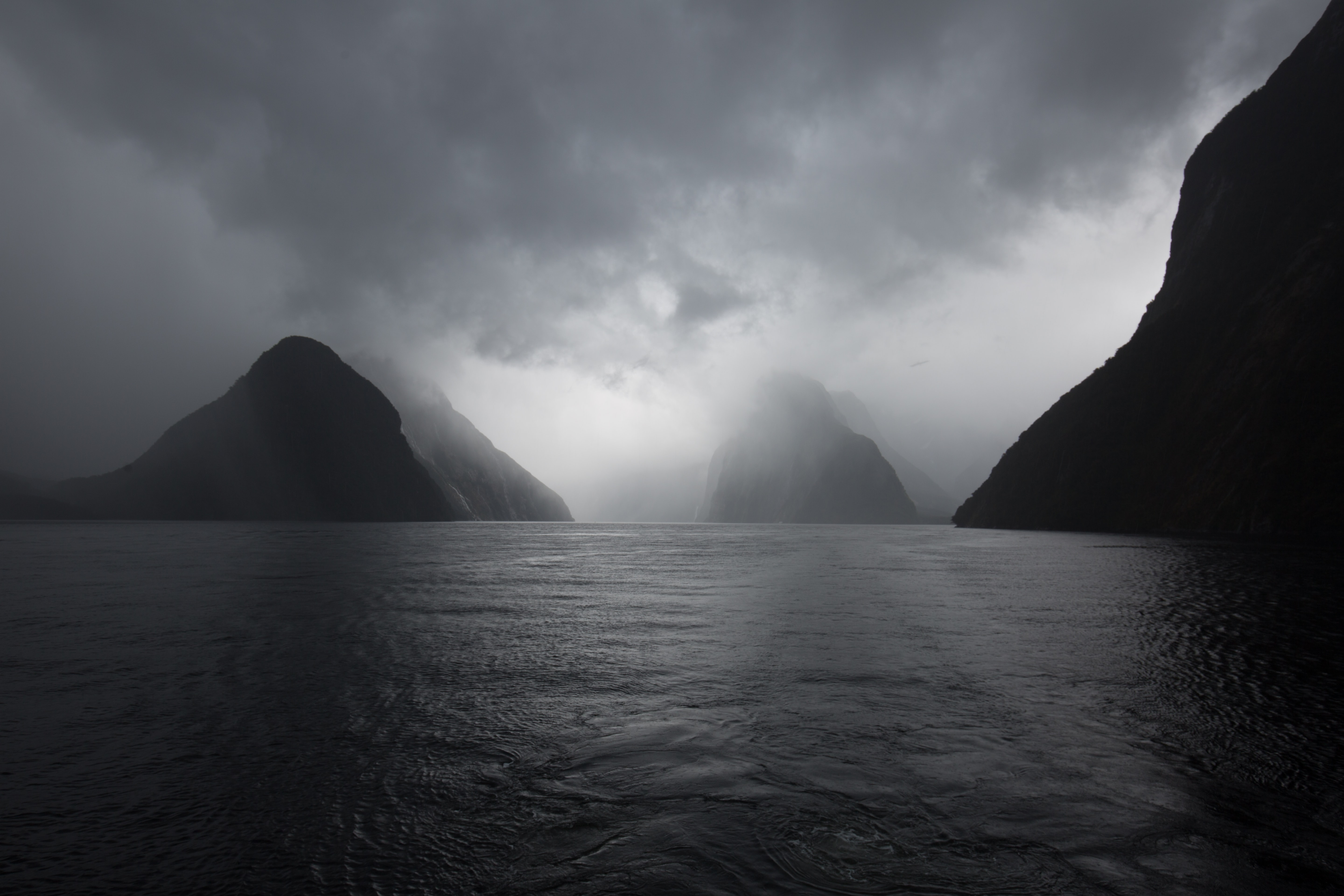 landscape photography of body of water under gray sky