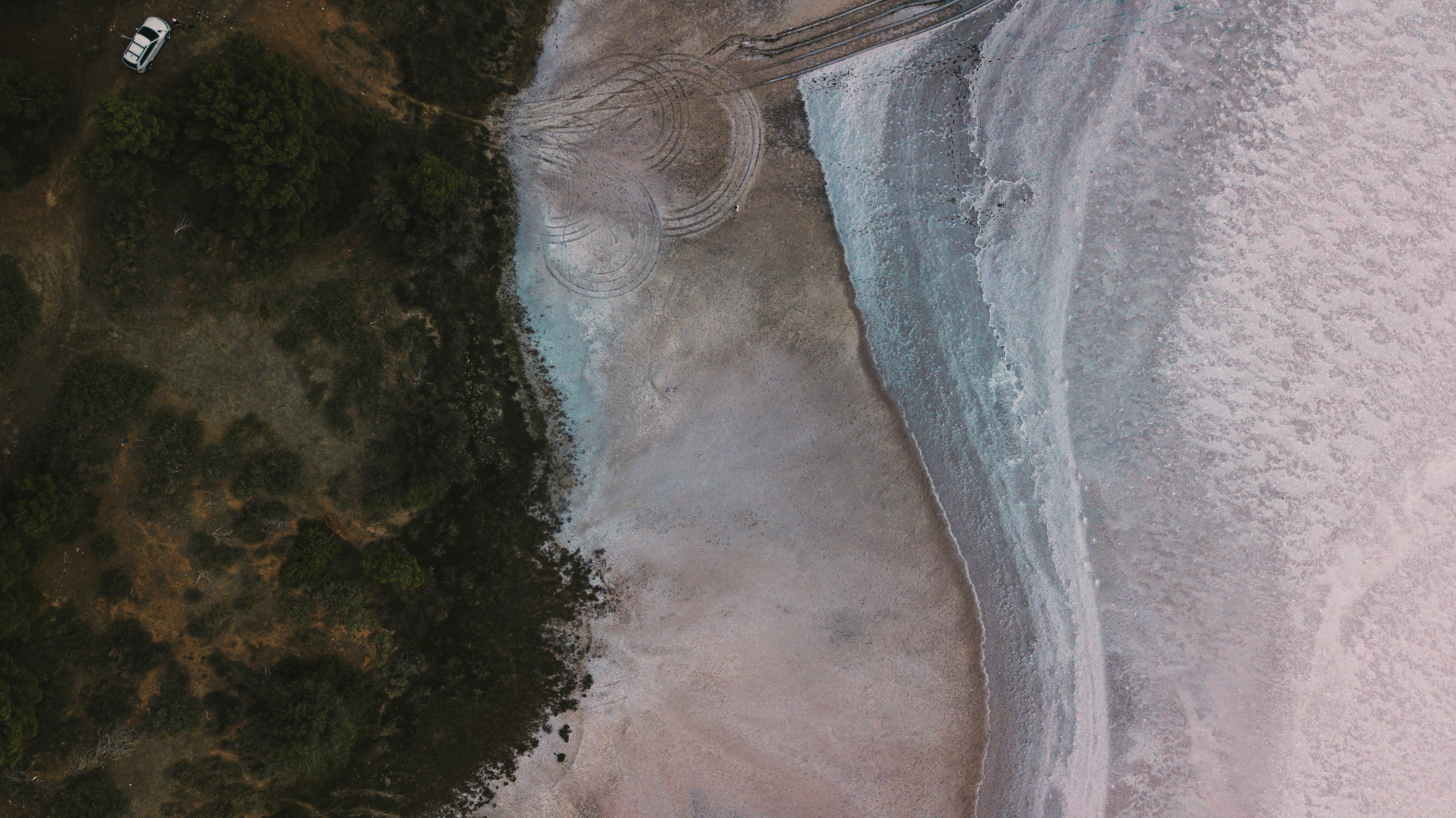 aerial photography of white vehicle running on rough road near shore
