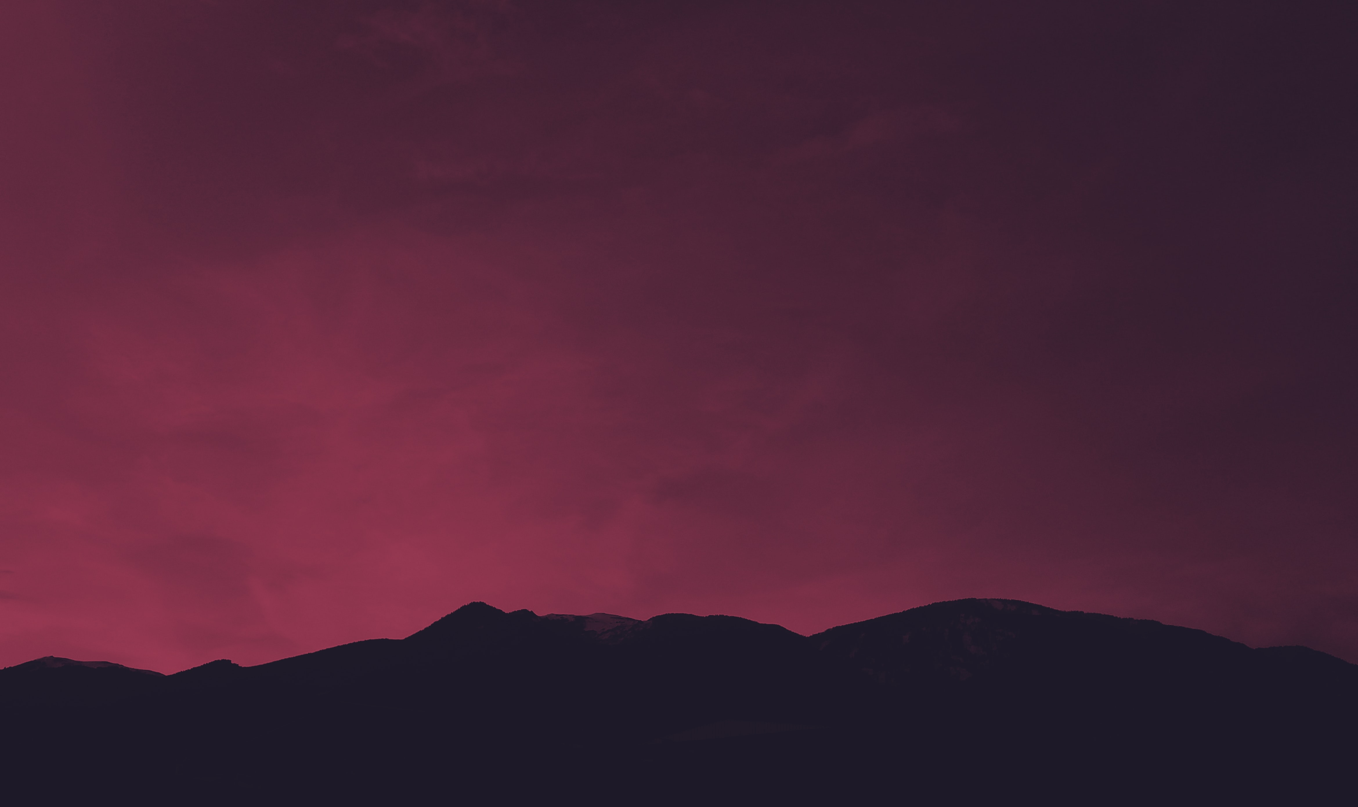silhouette of mountain under red sky