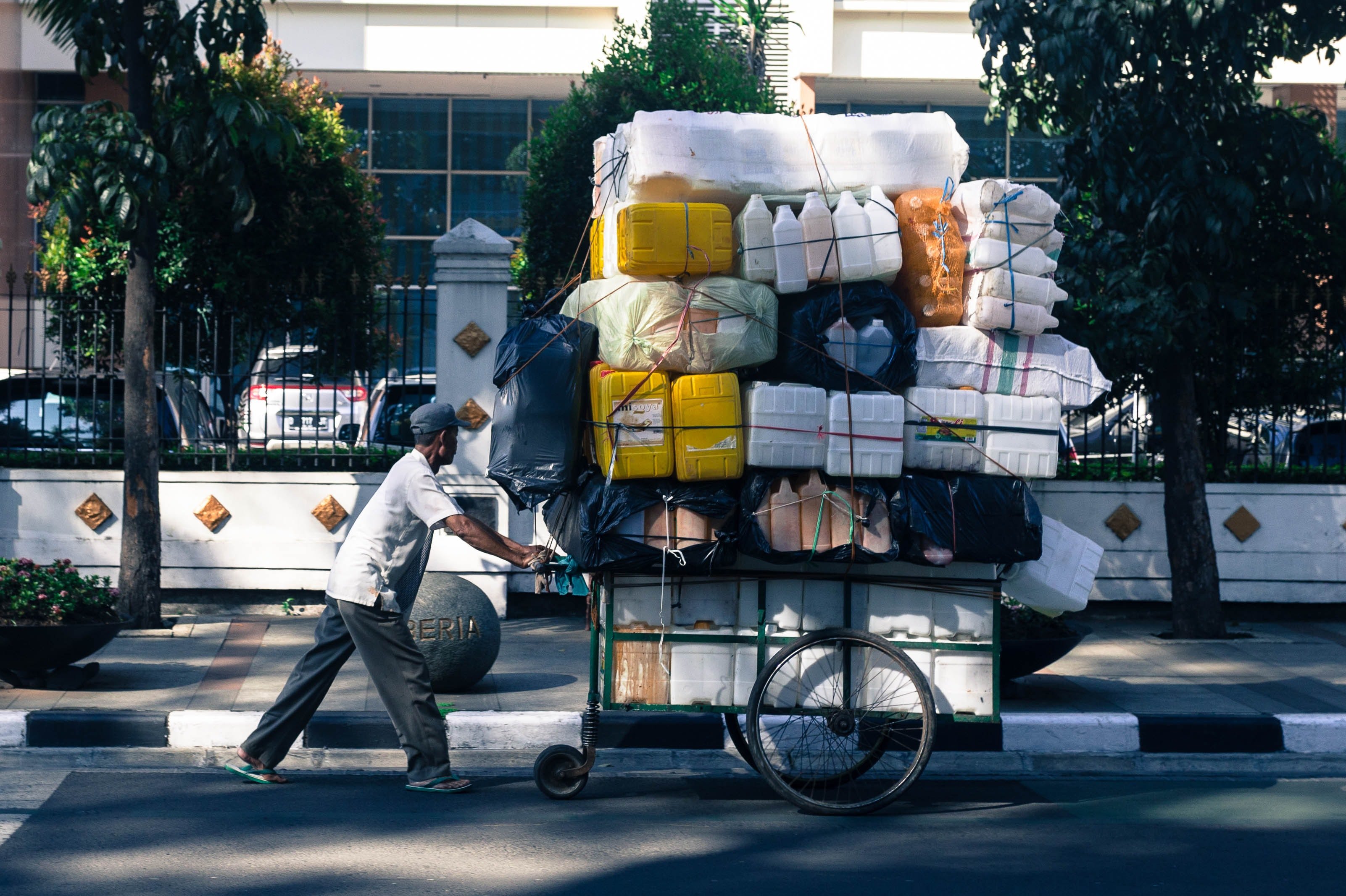 man pushing cart with containers